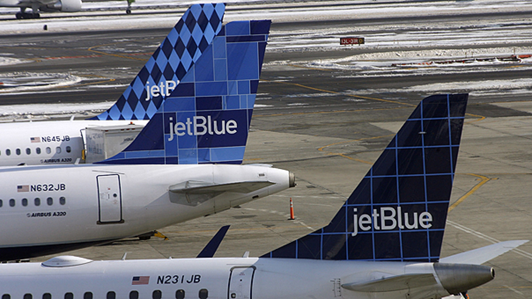 In this Feb. 20, 2007 file photo, JetBlue airplanes display their registration numbers along the windows at the rear of the aircraft at John F. Kennedy International Airport in New York.