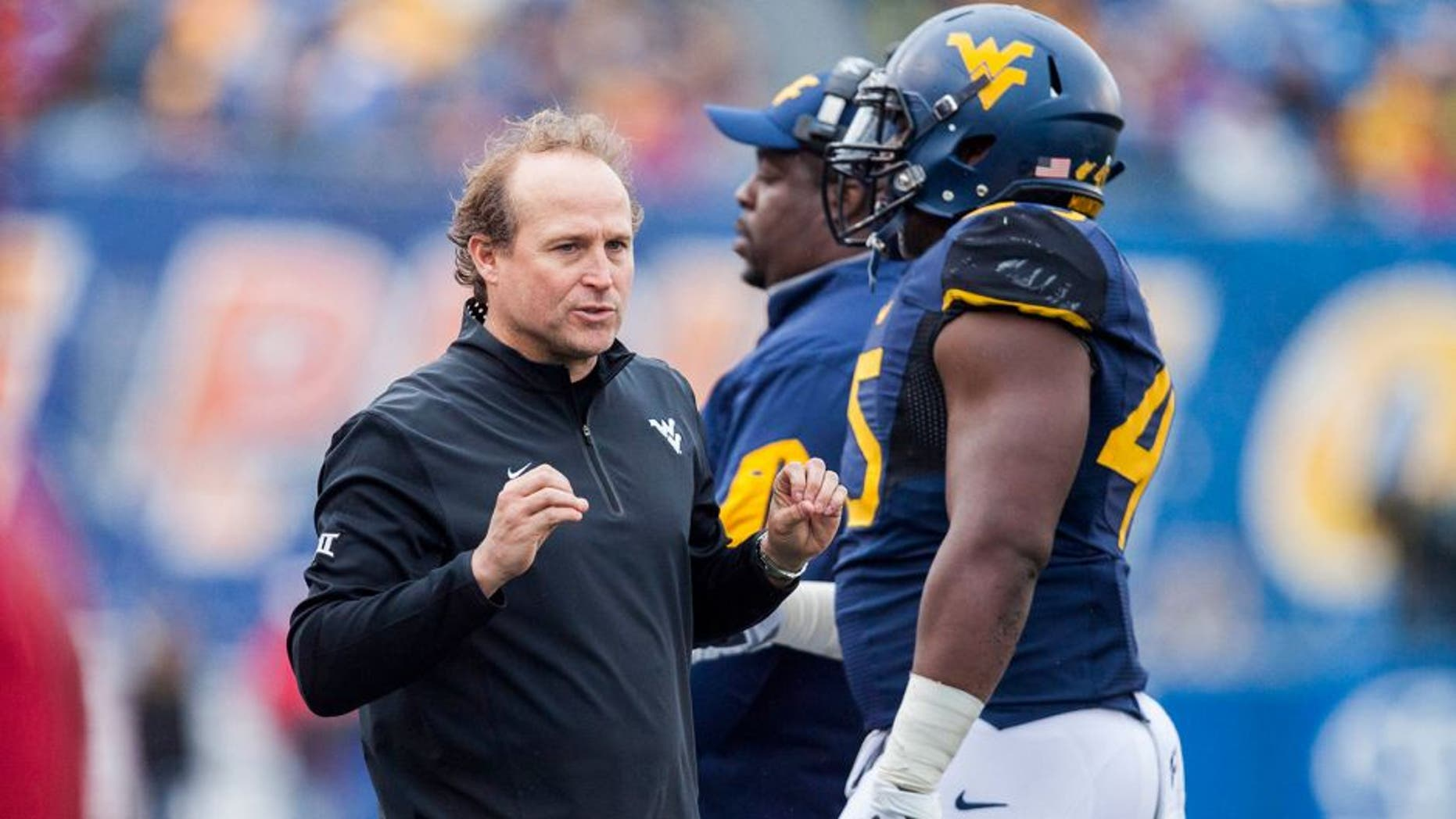 Nov 28, 2015; Morgantown, WV, USA; West Virginia Mountaineers head coach Dana Holgorsen talks with players on the sideline during the second quarter against the Iowa State Cyclones at Milan Puskar Stadium. Mandatory Credit: Ben Queen-USA TODAY Sports