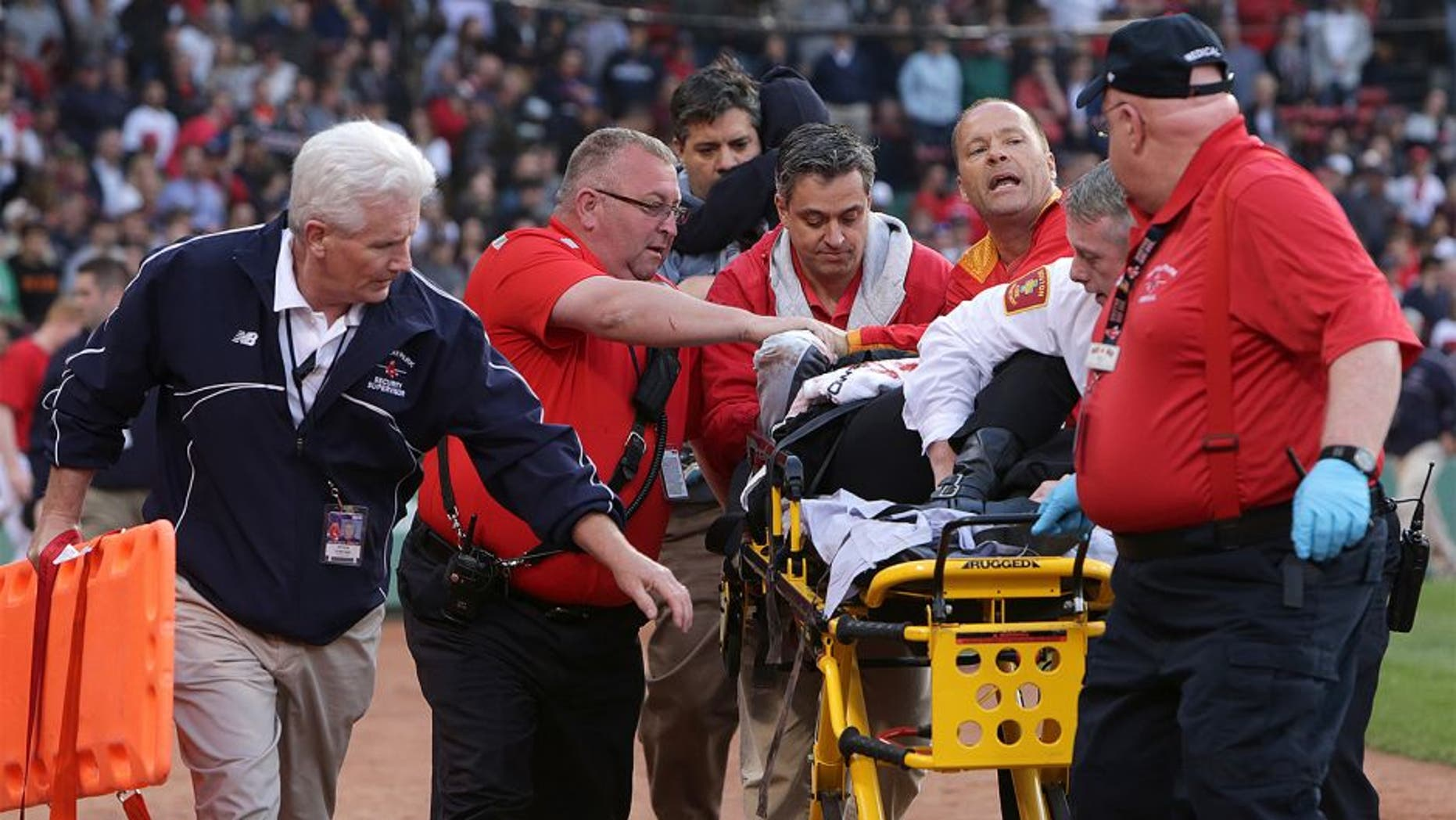 BOSTON - JUNE 5: Medical personnel remove a fan injured by a broken bat in the second inning. The Boston Red Sox take on the Oakland Athletics in Game 1 of a three game series at Fenway Park. (Photo by Barry Chin/The Boston Globe via Getty Images)