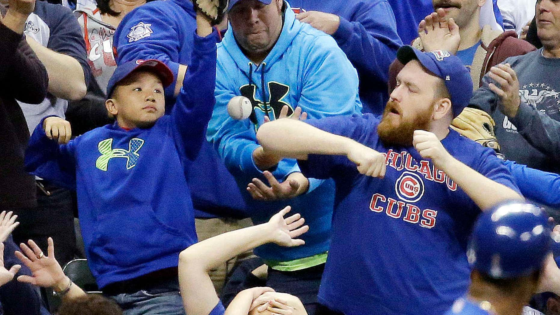 FILE - In this Oct. 2, 2015, file photo, fans go after a foul ball hit by Chicago Cubs' Dexter Fowler during the third inning of a baseball game against the Milwaukee Brewers, in Milwaukee.