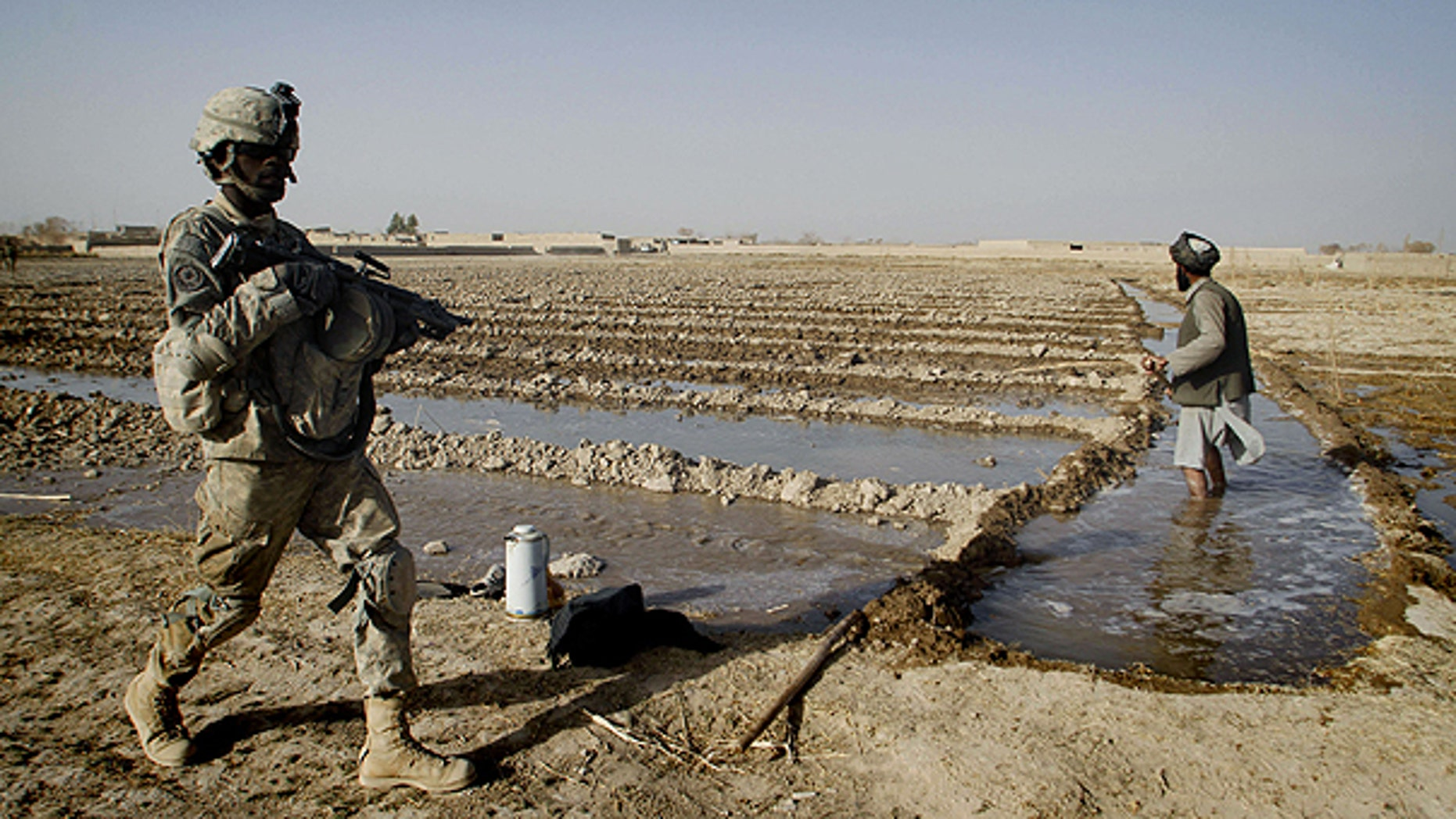 Dec. 8: A U.S. soldier passes by an Afghan farmer, who waters his farming lands during a patrol in Panjwai district of Kandahar province, south of Kabul, Afghanistan.