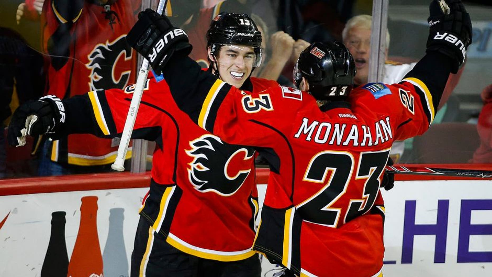 Calgary Flames' Johnny Gaudreau, left, celebrates his game-winning goal with teammate Sean Monahan during third period NHL hockey action against the Buffalo Sabres, in Calgary, on Thursday, Dec. 10, 2015. (Jeff McIntosh/The Canadian Press via AP) MANDATORY CREDIT