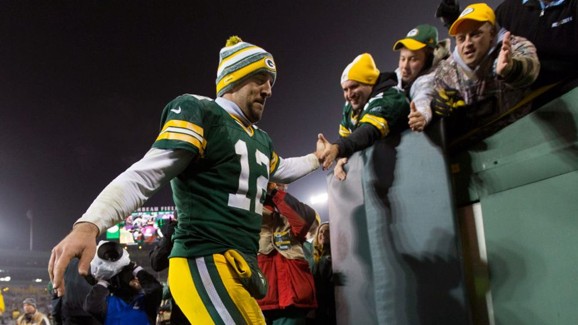 Dec 8, 2014; Green Bay, WI, USA; Green Bay Packers quarterback Aaron Rodgers (12) high fives fans following the game against the Atlanta Falcons at Lambeau Field. Green Bay won 43-37. Mandatory Credit: Jeff Hanisch-USA TODAY Sports