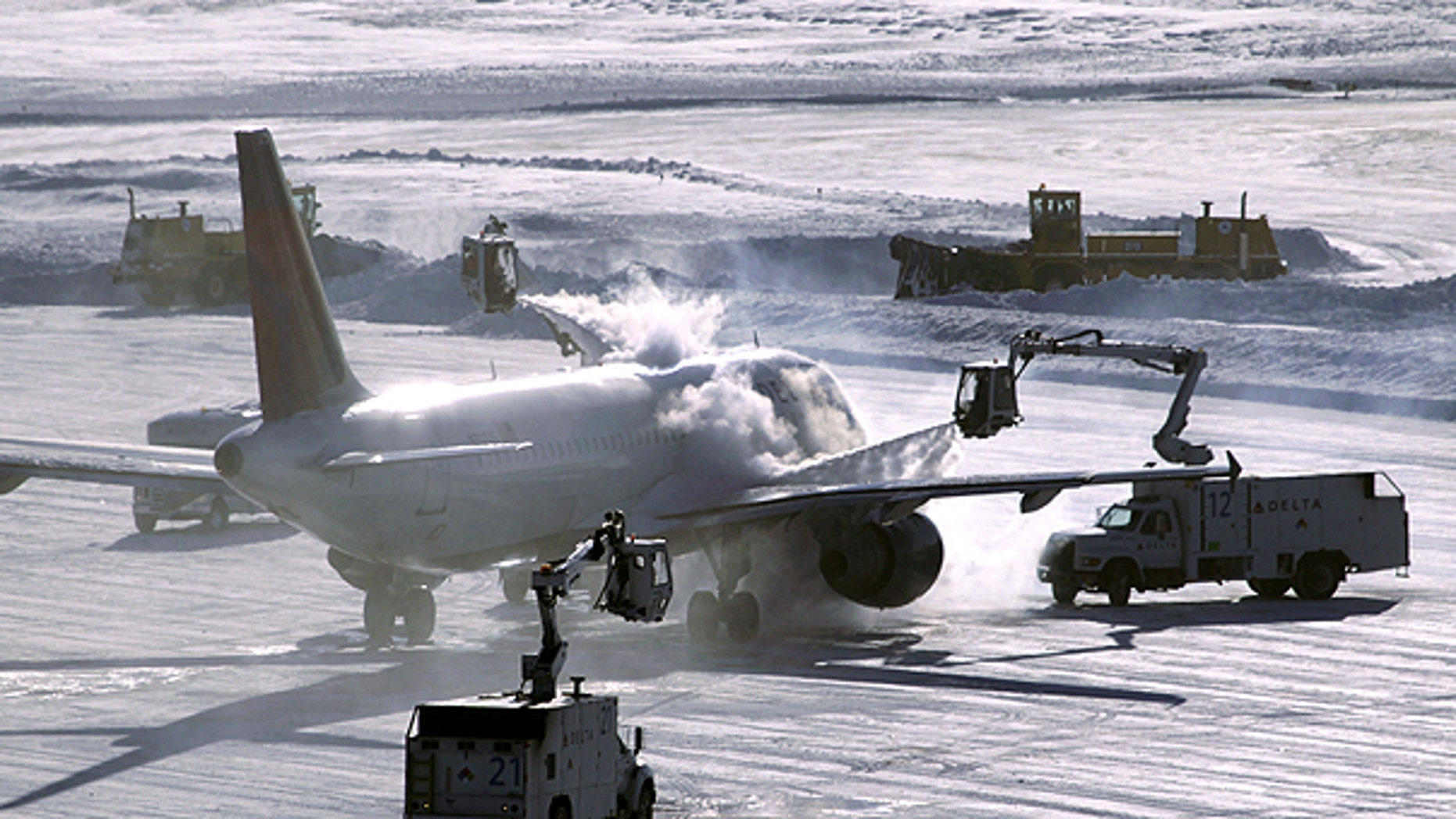 Dec. 12: A plane is de-iced before take-off while snowplows clear the runway at Minneapolis-St. Paul International Airport in Minneapolis.