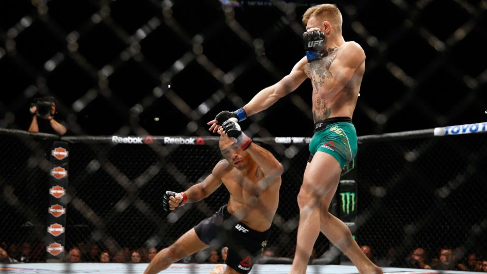 LAS VEGAS, NV - DECEMBER 12: (R-L) Conor McGregor of Ireland punches Jose Aldo of Brazil in their UFC featherweight championship bout during the UFC 194 event inside MGM Grand Garden Arena on December 12, 2015 in Las Vegas, Nevada. (Photo by Christian Petersen/Zuffa LLC/Zuffa LLC via Getty Images)