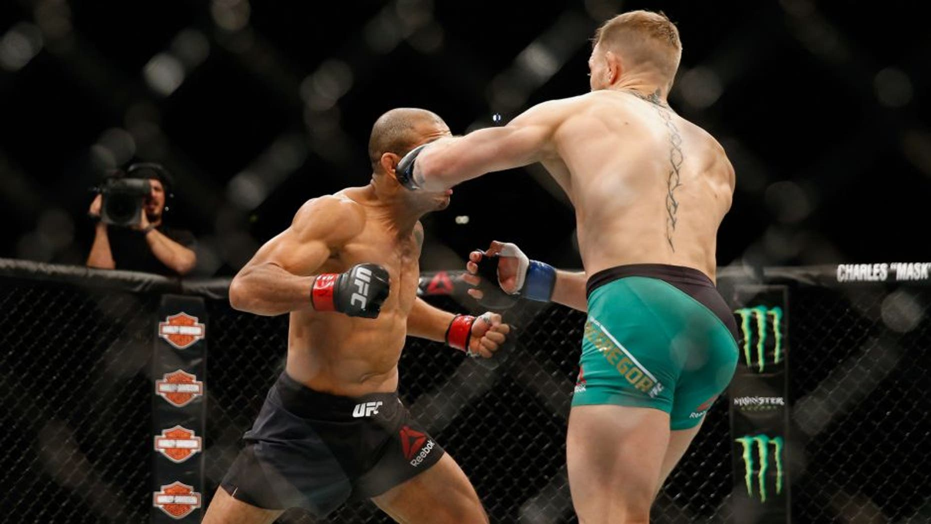 LAS VEGAS, NV - DECEMBER 12: (R-L) Conor McGregor of Ireland punches Jose Aldo of Brazil in their UFC welterweight championship bout during the UFC 194 event inside MGM Grand Garden Arena on December 12, 2015 in Las Vegas, Nevada. (Photo by Christian Petersen/Zuffa LLC/Zuffa LLC via Getty Images)