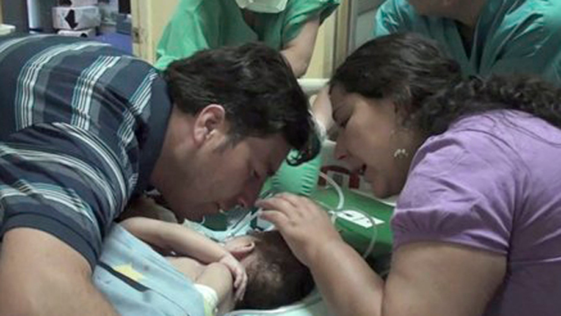 December 13, 2011: In this image taken from a video released by Luis Calvo Mackenna hospital, Jessica Navarrete, right, and Roberto Paredes, parents of conjoined twins Maria Paz and Maria Jose Paredes Navarrete kiss them before a separation surgery in Santiago, Chile.