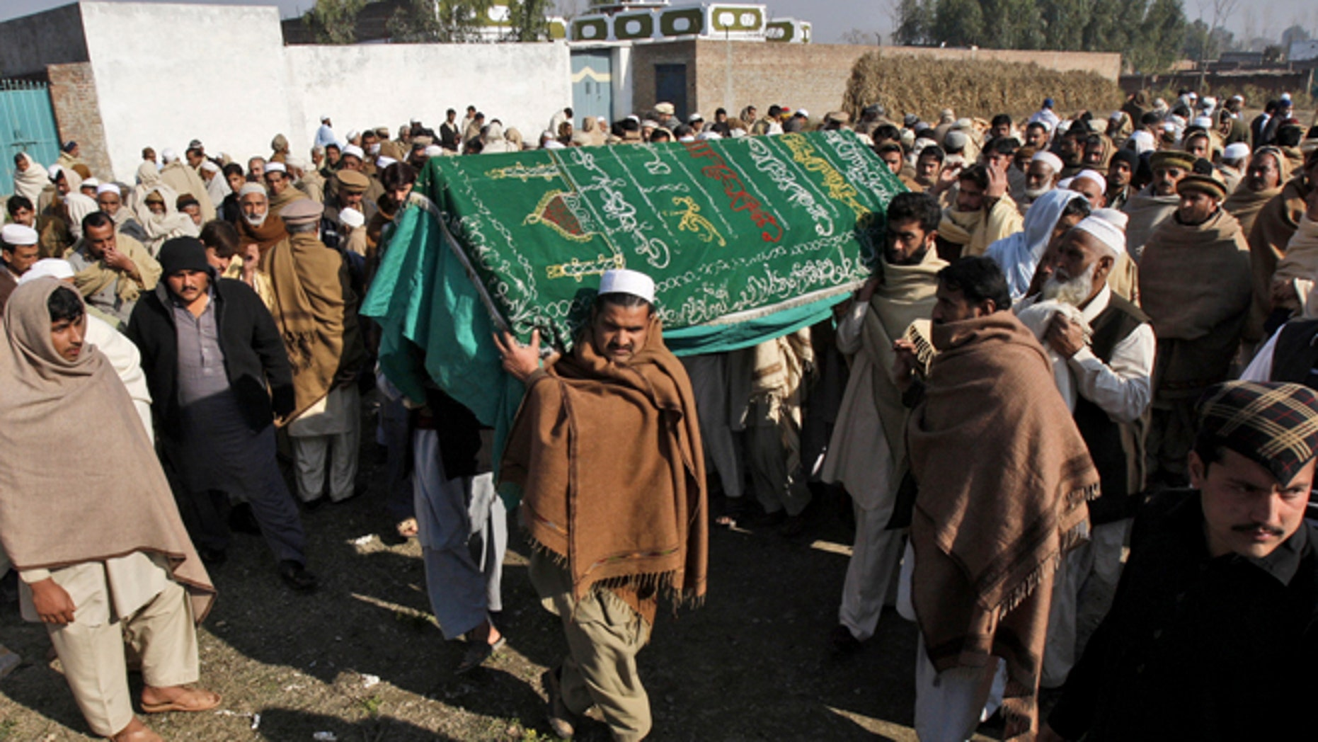 Jan. 2, 2013: Pakistani relatives and mourners carry the body of aid worker Lubna Mahmoud, 26, who was killed on Tuesday, by gunmen, during her funeral procession in Swabi, Pakistan.