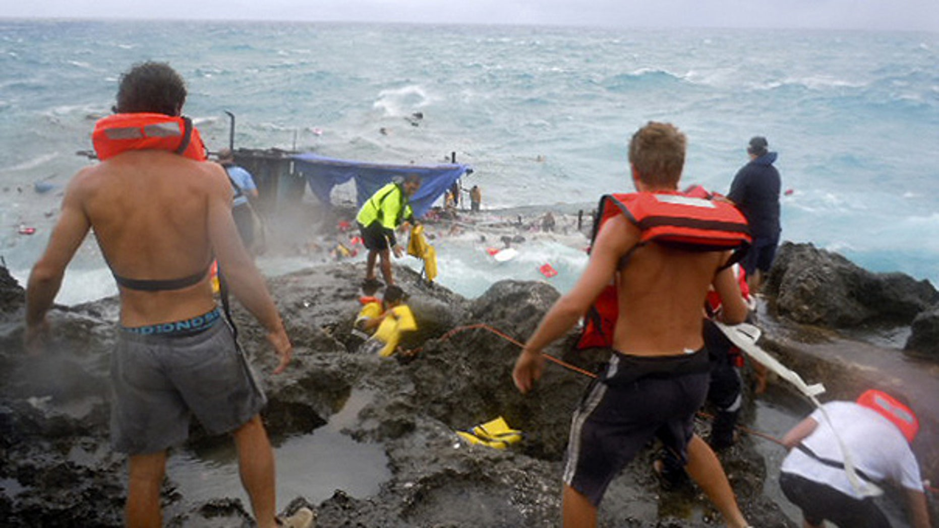 Dec. 15: People clamber on the rocky shore on Christmas Island during a rescue attempt as a boat smashes into rocks.