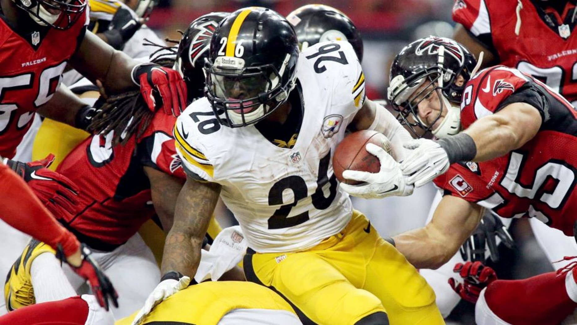 Dec 14, 2014; Atlanta, GA, USA; Pittsburgh Steelers running back Le'Veon Bell (26) fights for extra yards against Atlanta Falcons inside linebacker Paul Worrilow (55) and others in the fourth quarter of their game at the Georgia Dome. The Steelers won 27-20. Mandatory Credit: Jason Getz-USA TODAY Sports