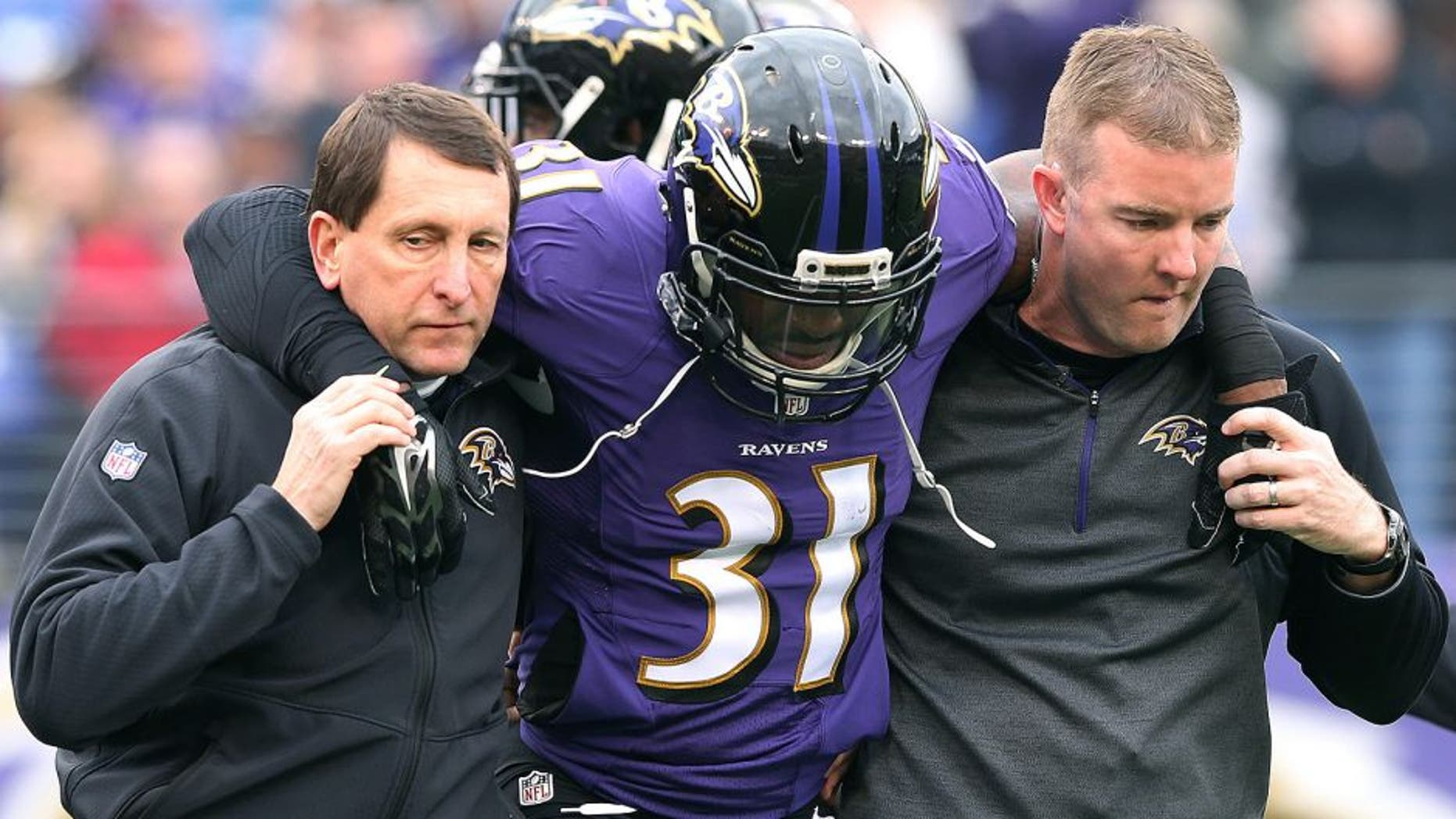 Dec 14, 2014; Baltimore, MD, USA; Baltimore Ravens safety Terrence Brooks (31) is assisted off the field after suffering an apparent injury on the opening kickoff against the Jacksonville Jaguars at M&T Bank Stadium. Mandatory Credit: Mitch Stringer-USA TODAY Sports