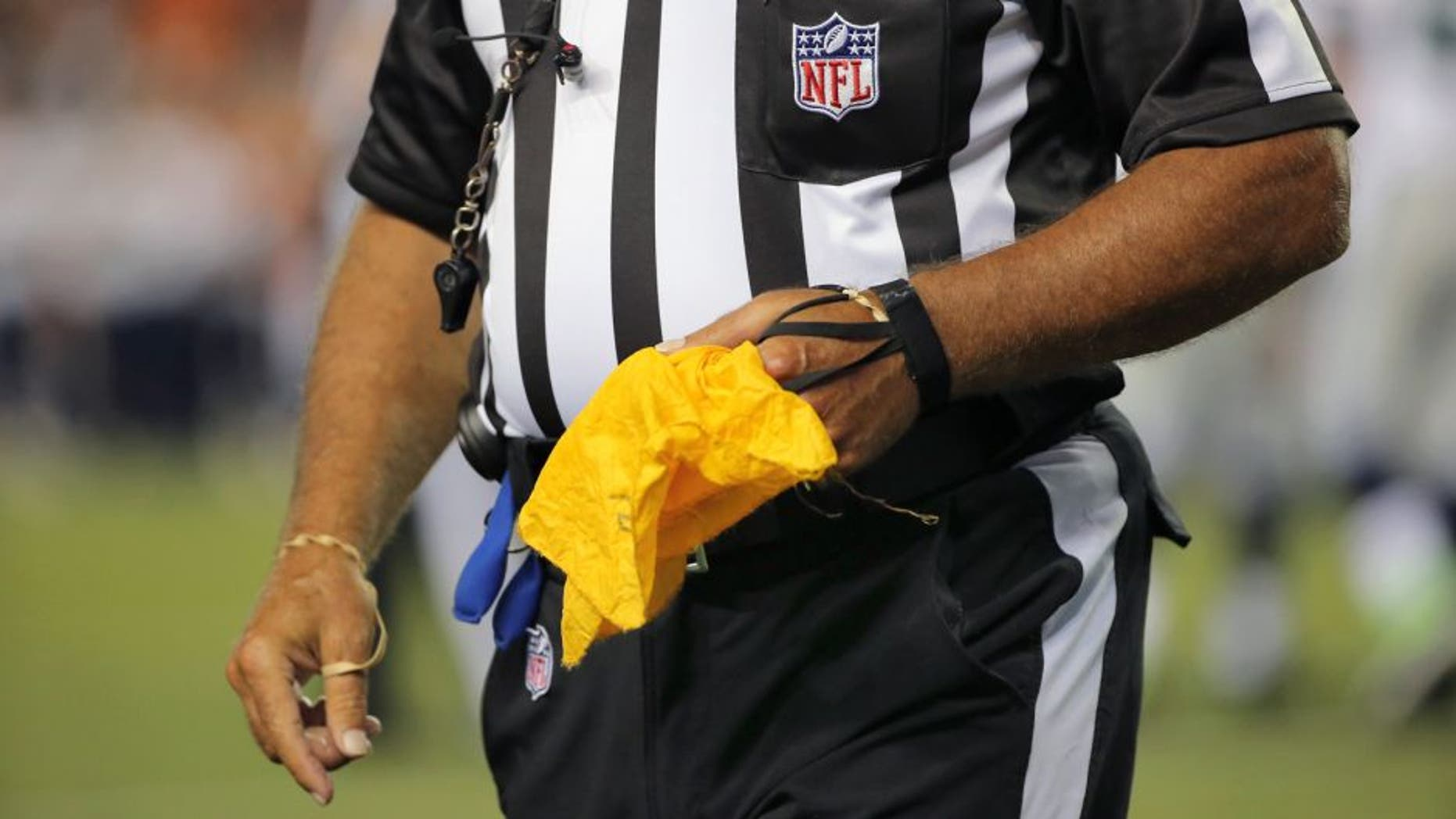 DENVER, CO - AUGUST 07: A referee collects his penalty flag as the Seattle Seahawks face the Denver Broncos during preseason action at Sports Authority Field at Mile High on August 7, 2014 in Denver, Colorado. The Broncos defeated the Seahawks 21-16. (Photo by Doug Pensinger/Getty Images)