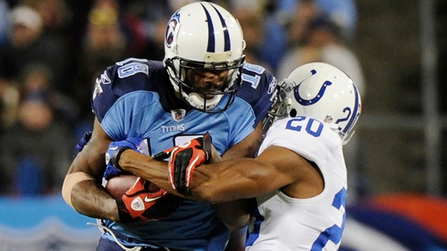 Tennessee Titans wide receiver Kenny Britt (18) hangs on to a pass as he is hit by Indianapolis Colts cornerback Justin Tryon (20) in the first quarter of an NFL football game on Thursday, Dec. 9, 2010, in Nashville, Tenn.
