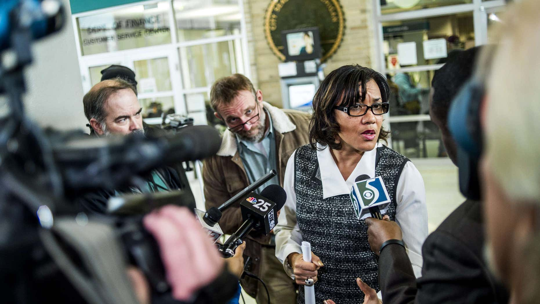 Dec. 15, 2015: A swarm of reporters surround Flint Mayor Karen Weaver to ask question after a news conference at City Hall in Flint, Mich.