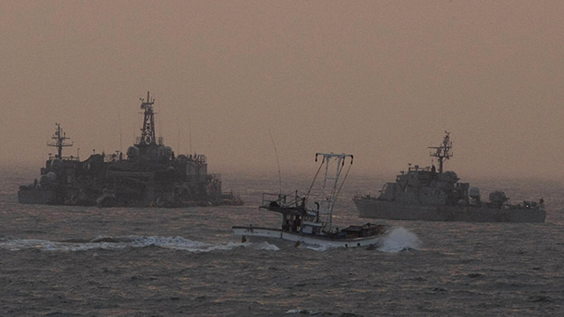 Dec. 19: A South Korean fishing boat sails by a South Korean navy facility and navy ship near Yeonpyeong island, South Korea.
