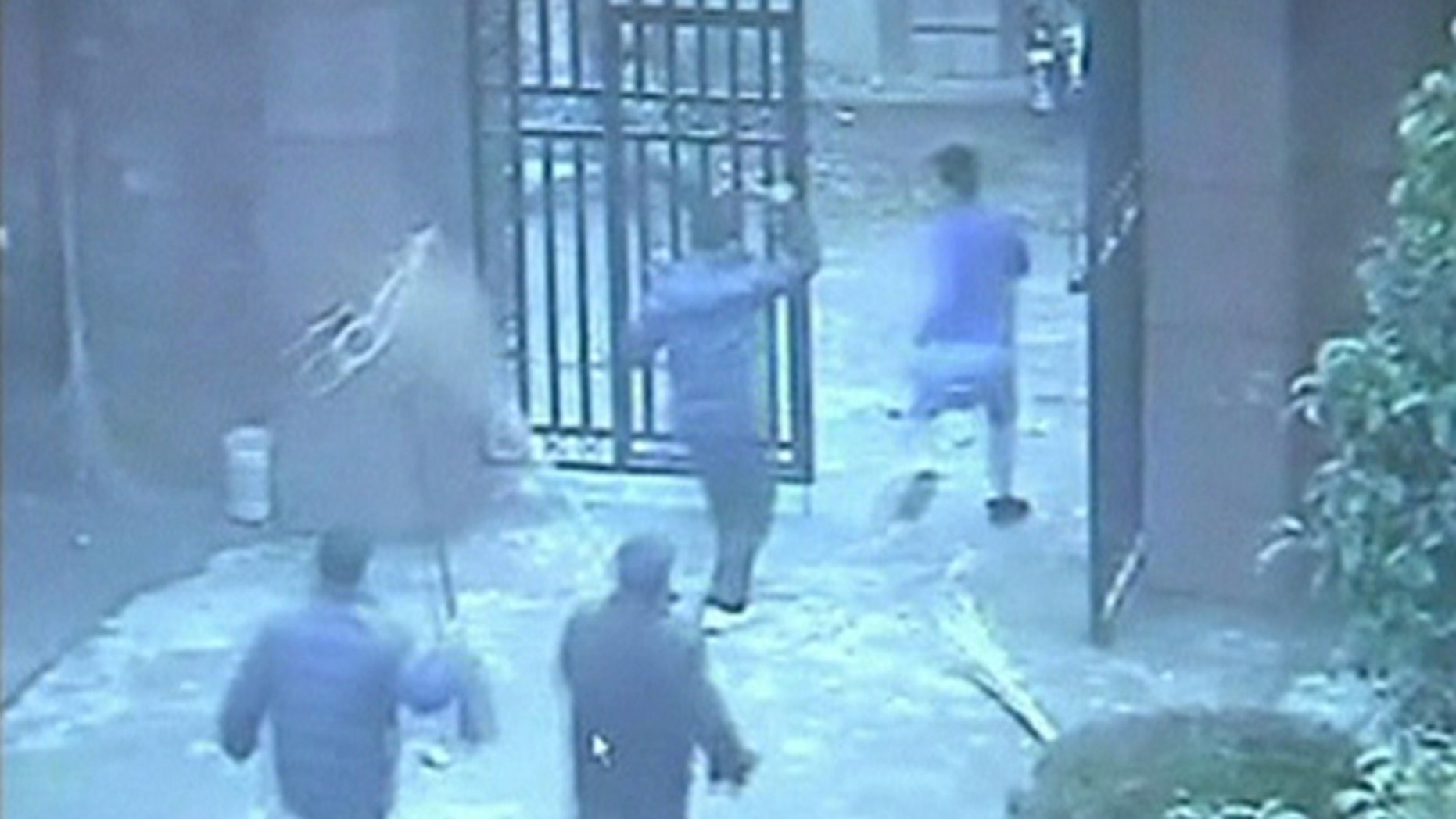 People chase a man (R), who attacked students with a knife, out of an elementary school in Guangshan county, Henan province, in this still image from a December 14, 2012 surveillance video, released by local police December 18, 2012.