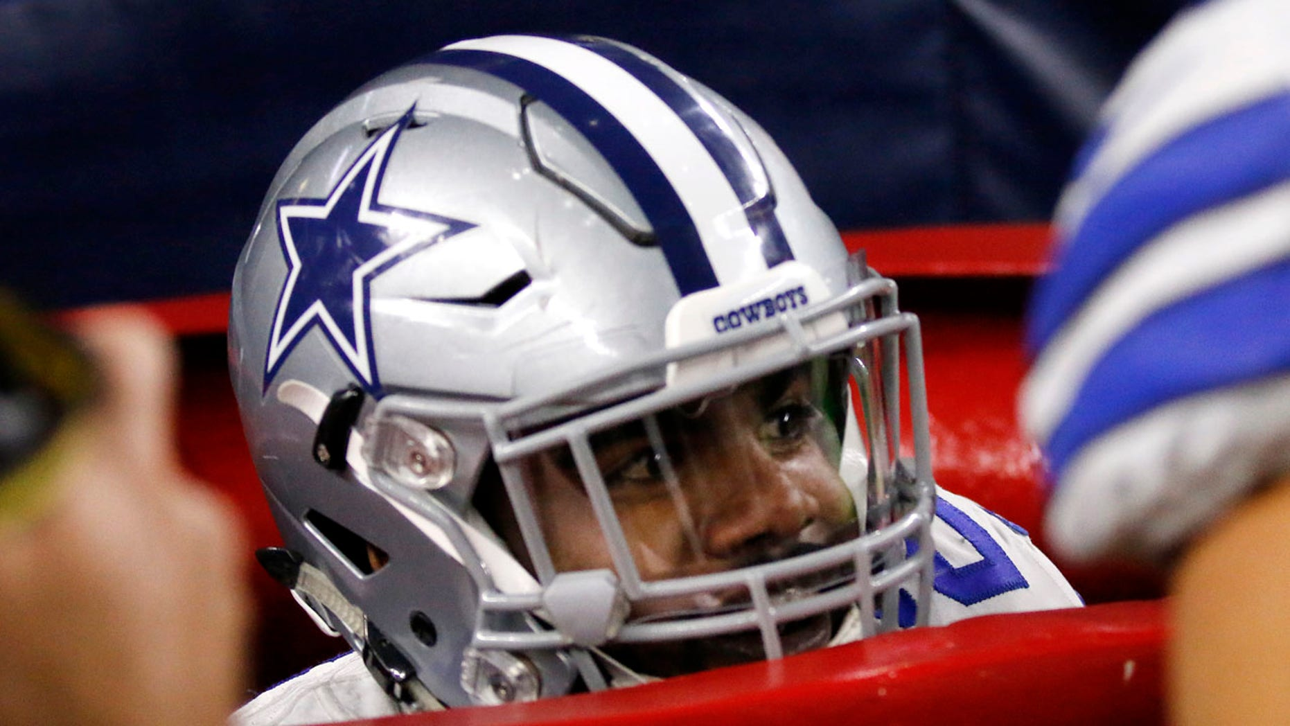 Dallas Cowboys running back Ezekiel Elliott peeks out of a large Salvation Army kettle after jumping into it celebrating a touchdown he scored on a running play in the first half of an NFL football game against the Tampa Bay Buccaneers on Sunday, Dec. 18, 2016, in Arlington, Texas.