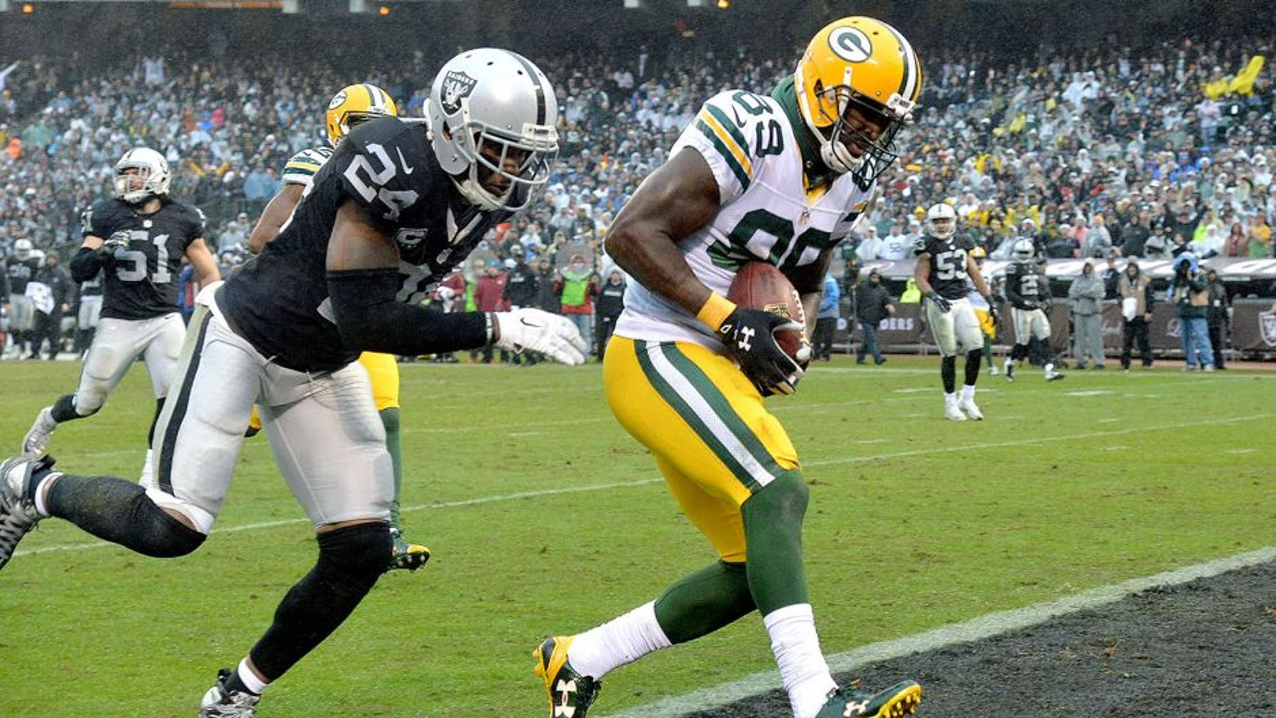 Dec 20, 2015; Oakland, CA, USA; Green Bay Packers wide receiver James Jones (89) is defended by Oakland Raiders free safety Charles Woodson (24) on a 30-yard touchdown reception in the third quarter during an NFL football game at O.co Coliseum. The Packers defeated the Raiders 30-20. Mandatory Credit: Kirby Lee-USA TODAY Sports
