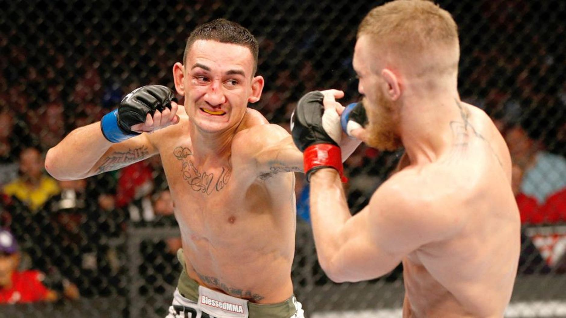 BOSTON, MA - AUGUST 17: (L-R) Max Holloway punches Conor McGregor in their UFC featherweight bout at TD Garden on August 17, 2013 in Boston, Massachusetts. (Photo by Josh Hedges/Zuffa LLC/Zuffa LLC via Getty Images)