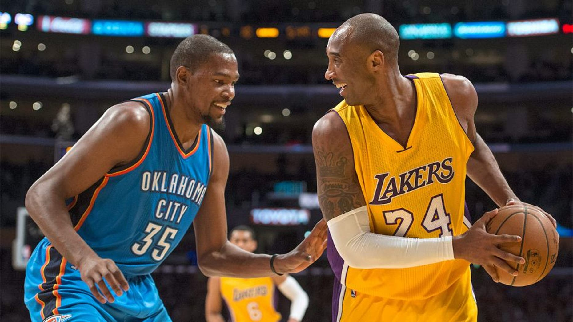 Los Angeles Lakers' Kobe Bryant, right, smiles with Oklahoma City Thunder's Kevin Durant during an NBA basketball game Wednesday, Dec. 23, 2015, in Los Angeles. (Kyusung Gong/The Orange County Register via AP)