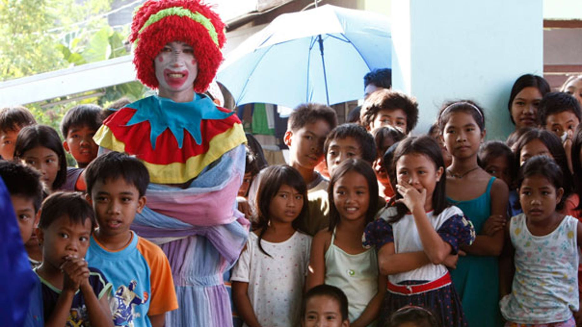 Dec. 25: An entertainer dressed as a clown watches another performance together with Mayon volcano children evacuees during a Christmas celebration at an evacuation center in Legazpi City, Philippines.