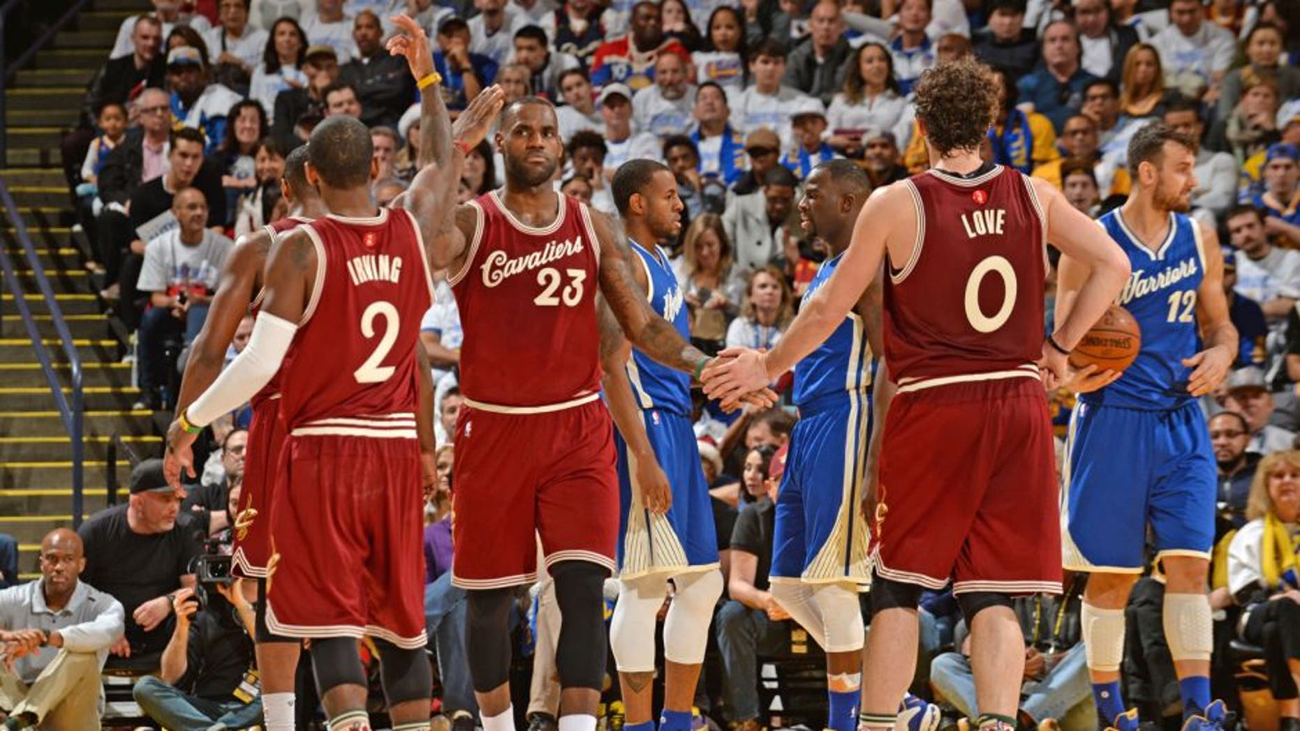 OAKLAND, CA - DECEMBER 25: LeBron James #23 and Kevin Love #0 and Kyrie Irving #2 of the Cleveland Cavaliers shake hands on against the Golden State Warriors on December 25, 2015 at ORACLE Arena in Oakland,California.NOTE TO USER: User expressly acknowledges and agrees that, by downloading and or using this Photograph, user is consenting to the terms and conditions of the Getty Images License Agreement. Mandatory Copyright Notice: Copyright 2015 NBAE (Photo by Noah Graham/NBAE via Getty Images)