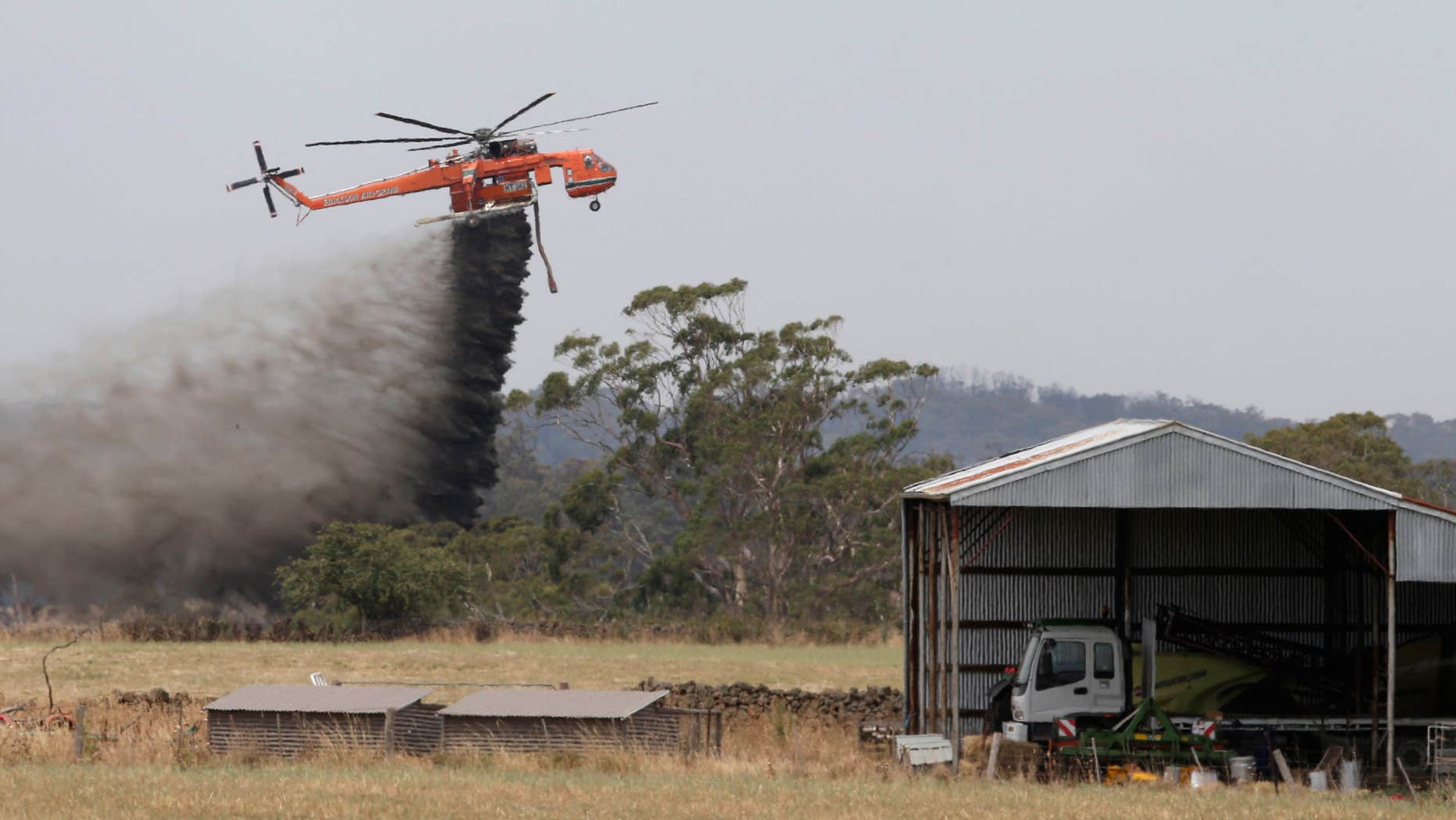 In this Sunday, Dec. 20, 2015 photo, a Skycrane helicopter drops a load of water as it works to hold back a wildfire from the hamlet of Claredon in Victoria, Australia.
