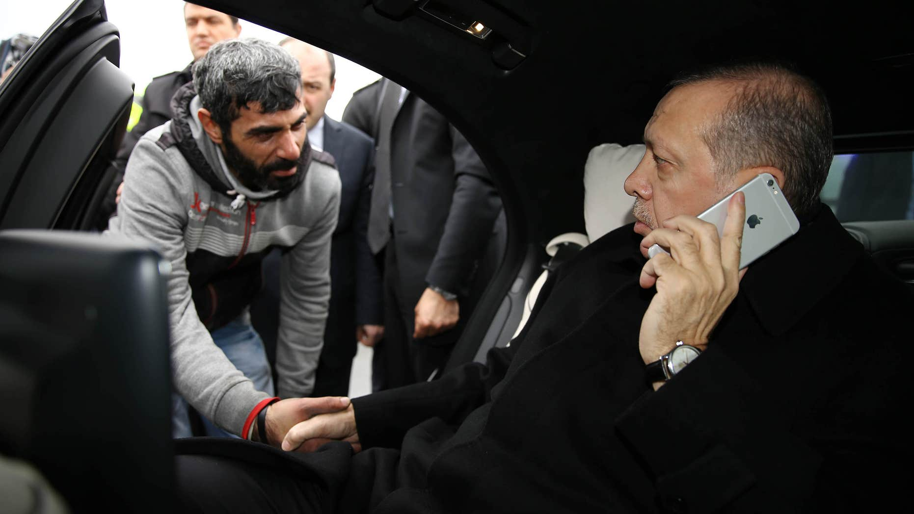 Dec. 25, 2015: Turkish President Recep Tayyip Erdogan, right, takes Vezir Cakras by hand while speaking on his mobile phone inside his car stationed over the Bosporus Bridge in Istanbul.