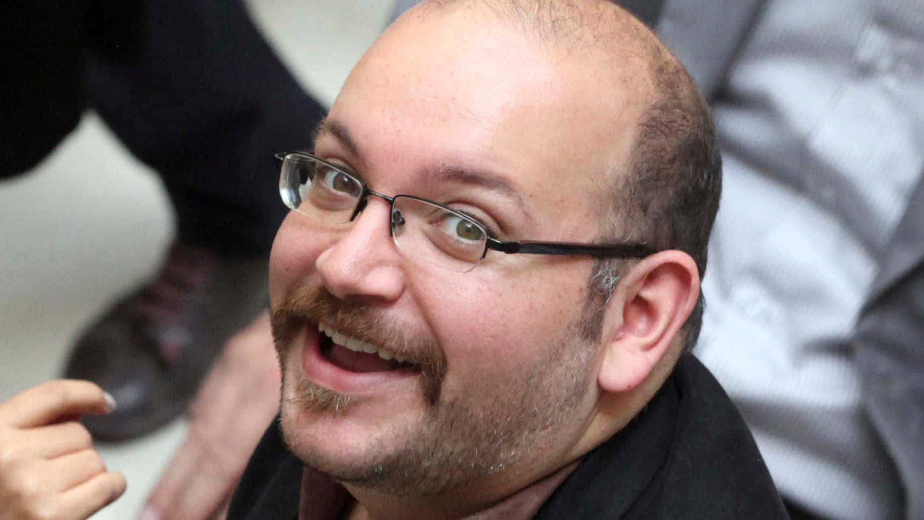 In this April 11, 2013 photo, Jason Rezaian, an Iranian-American correspondent for the Washington Post, smiles as he attends a presidential campaign of President Hassan Rouhani in Tehran, Iran.