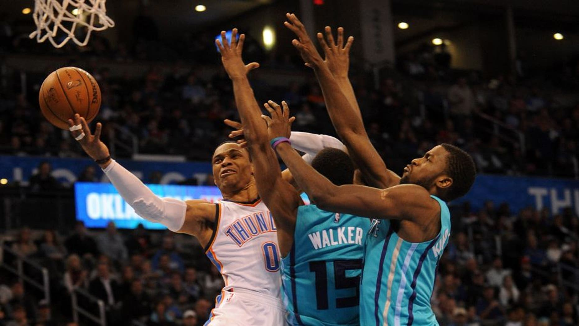 Dec 26, 2014; Oklahoma City, OK, USA; Oklahoma City Thunder guard Russell Westbrook (0) attempts a shot against Charlotte Hornets forward Michael Kidd-Gilchrist (14) and Hornets guard Kemba Walker (15) during the third quarter at Chesapeake Energy Arena. Mandatory Credit: Mark D. Smith-USA TODAY Sports