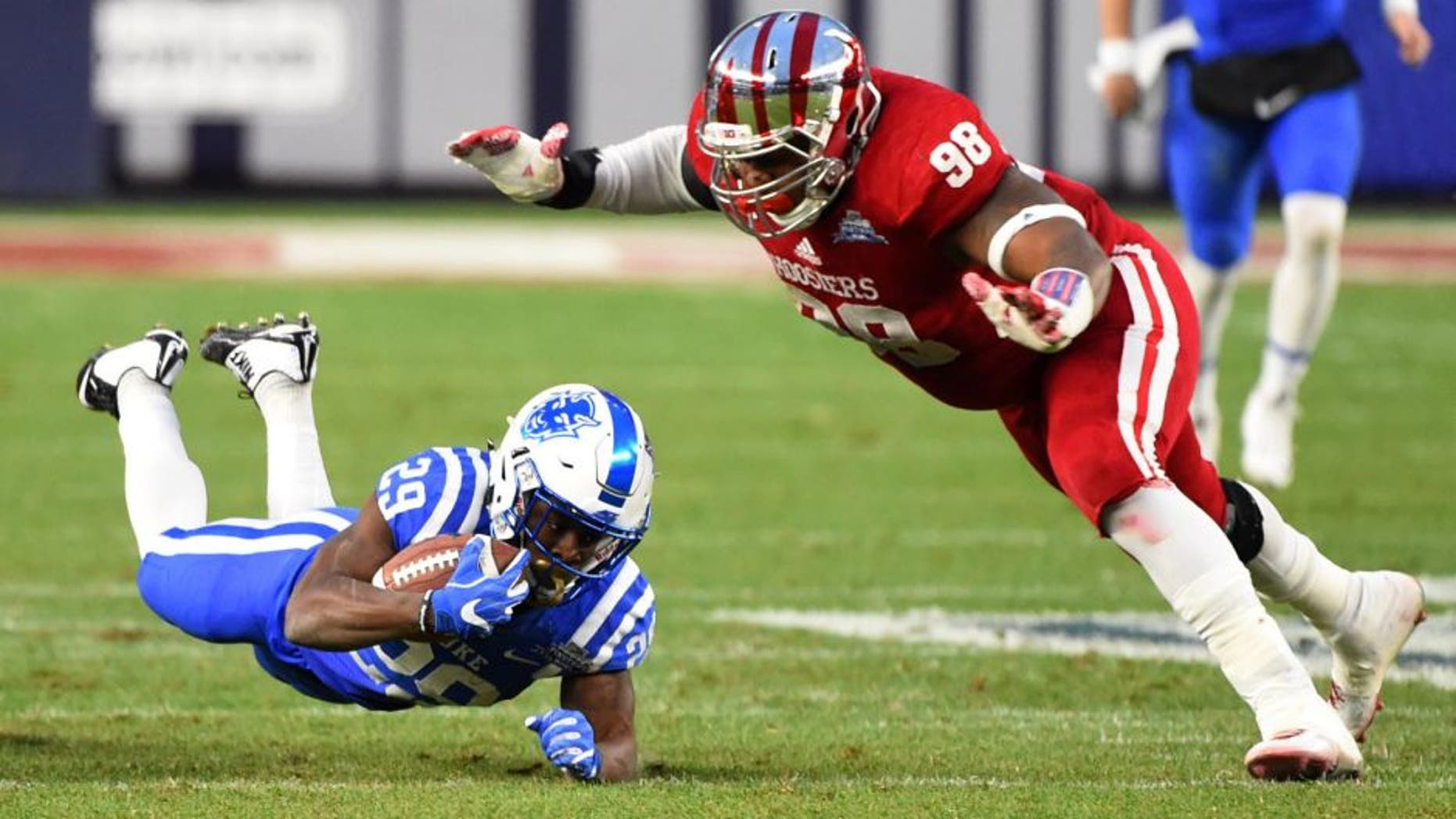 Dec 26, 2015; Bronx, NY, USA; Duke Blue Devils running back Shaun Wilson (29) dives for extra yards as Indiana Hoosiers defensive lineman Darius Latham (98) defends during the first quarter in the 2015 New Era Pinstripe Bowl at Yankee Stadium. Mandatory Credit: Rich Barnes-USA TODAY Sports