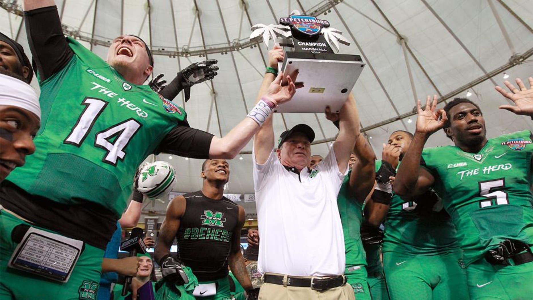 Dec 26, 2015; St. Petersburg, FL, USA; Marshall Thundering Herd head coach Doc Holliday raises the trophy with teammates after they beat the Connecticut Huskies to win the St. Petersburg Bowl at Tropicana Field. Marshall Thundering Herd defeated the Connecticut Huskies 16-10. Mandatory Credit: Kim Klement-USA TODAY Sports