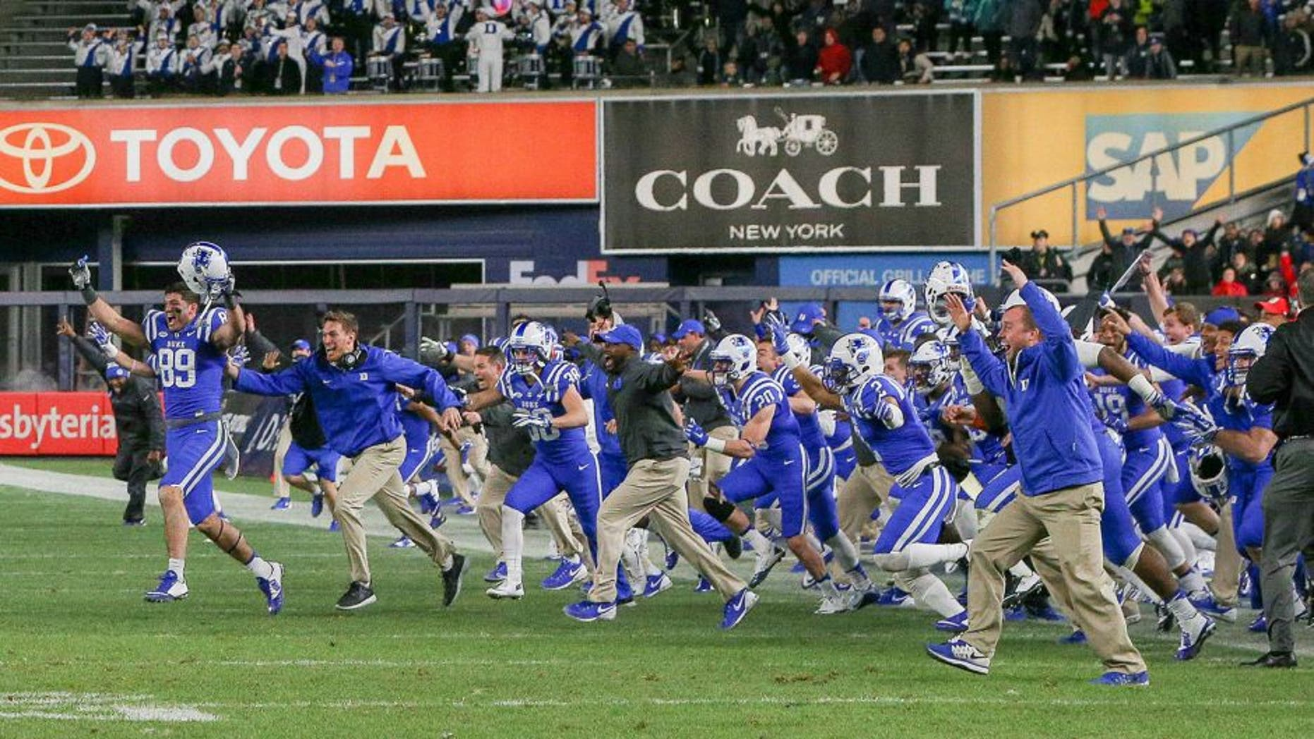 Dec 26, 2015; Bronx, NY, USA; The Duke Blue Devils players storms the field after the 2015 New Era Pinstripe Bowl against the Indiana Hoosiers at Yankee Stadium. The Blue Devils won 44-41 in overtime. Mandatory Credit: Vincent Carchietta-USA TODAY Sports