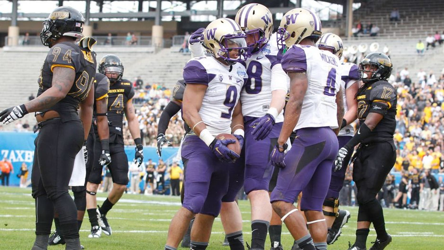 Dec 26, 2015; Dallas, TX, USA; Washington Huskies fullback Myles Gaskin (9) is congratulated after scoring a touchdown by tight end Drew Sample (88) and wide receiver Jaydon Mickens (4) in the first quarter against the Southern Miss Golden Eagles at Cotton Bowl Stadium. Mandatory Credit: Tim Heitman-USA TODAY Sports