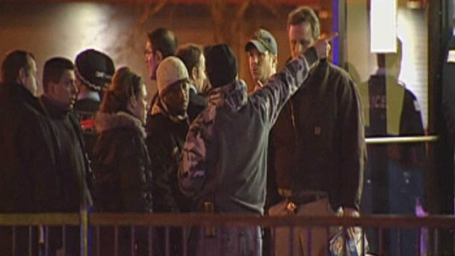 December 27, 2011: Onlookers stand outside the scene of a shooting in Chicago.