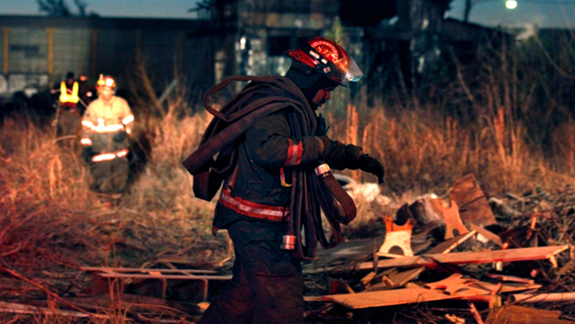 Dec. 28: Firefighters walk through debris after battling a fire in an abandoned warehouse, seen in background, in the Upper Ninth Ward of New Orleans.