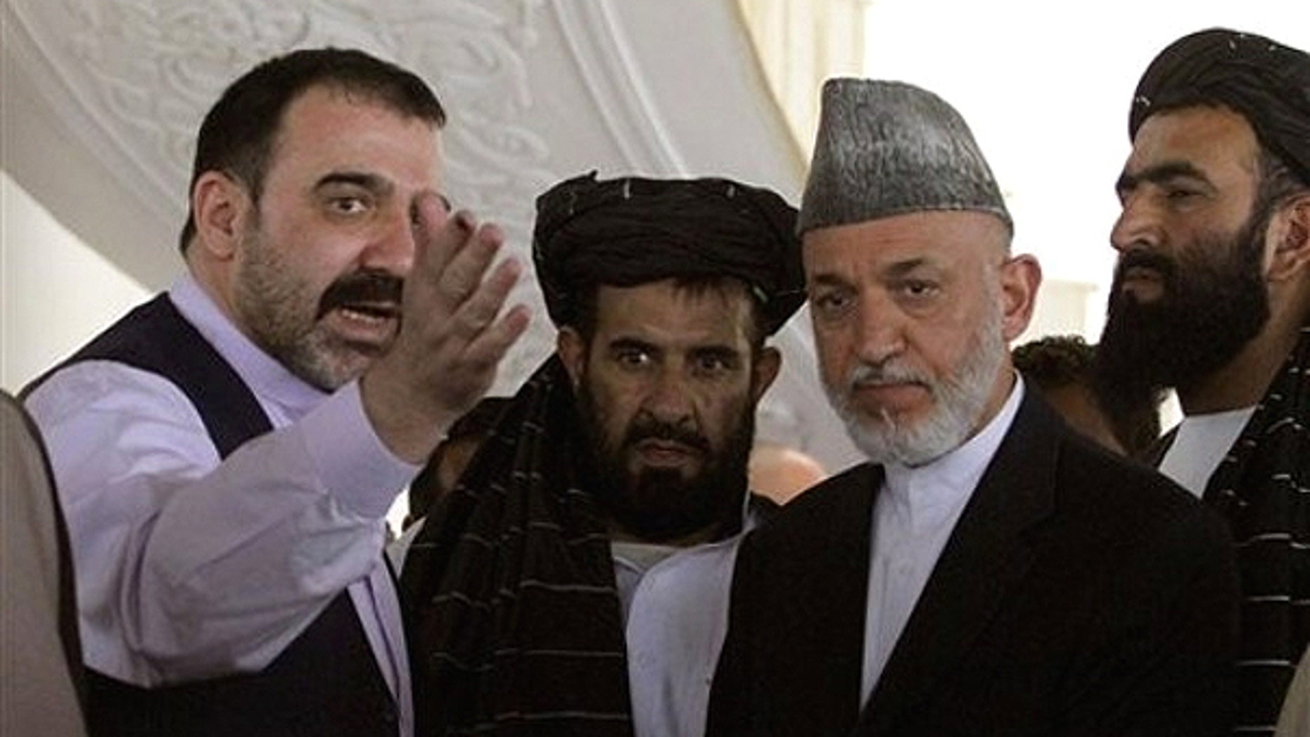 Oct. 9, 2010: Afghan President Hamid Karzai, second from right, is met by his half brother Ahmad Wali Karzai, left, in Argandab district of Kandahar province, south of Kabul, Afghanistan.
