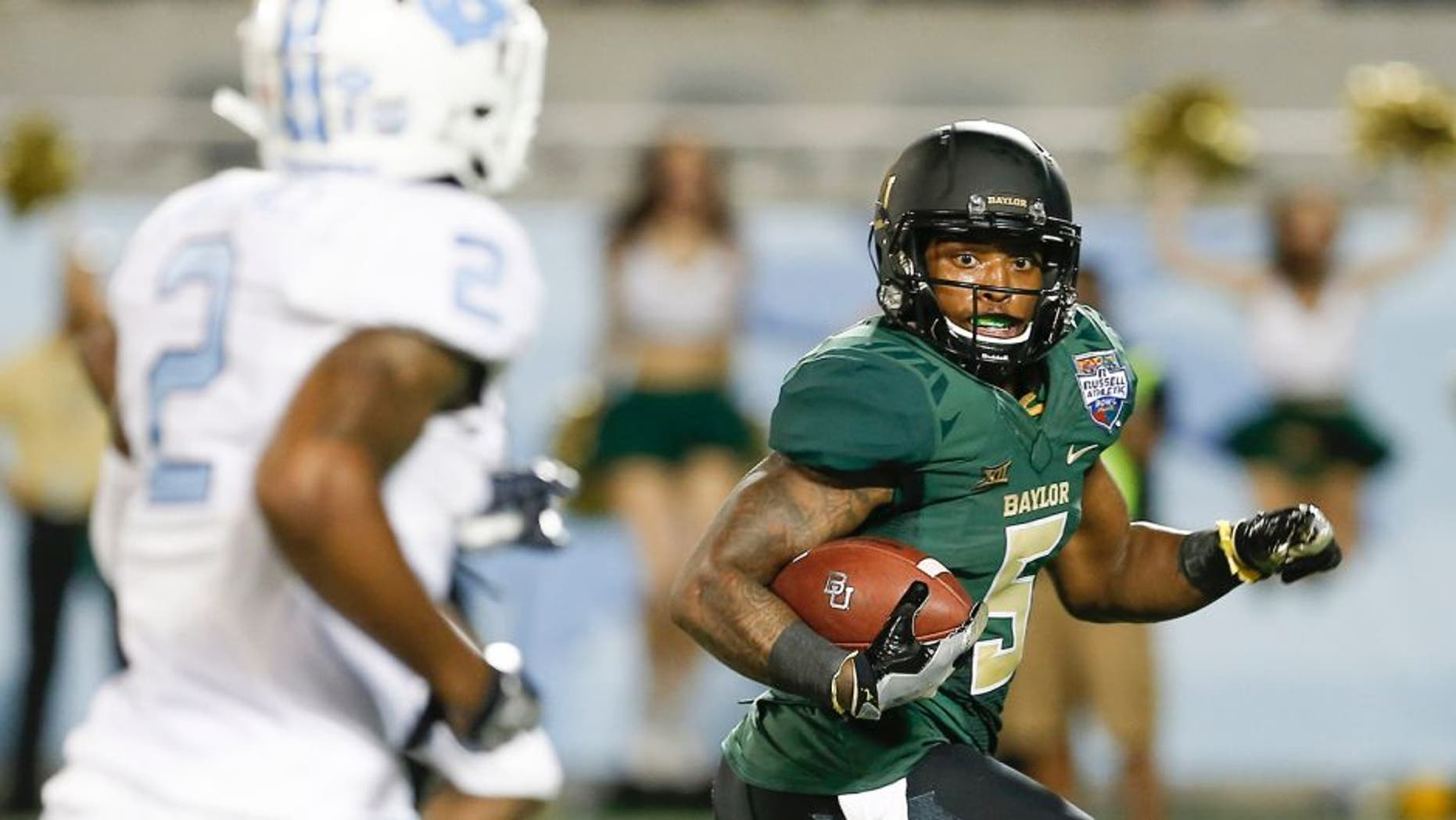 Dec 29, 2015; Orlando, FL, USA; Baylor Bears running back Johnny Jefferson (5) looks back at North Carolina Tar Heels cornerback Des Lawrence (2) before scoring on a touchdown run during the second quarter of a football game at Florida Citrus Bowl. Mandatory Credit: Reinhold Matay-USA TODAY Sports