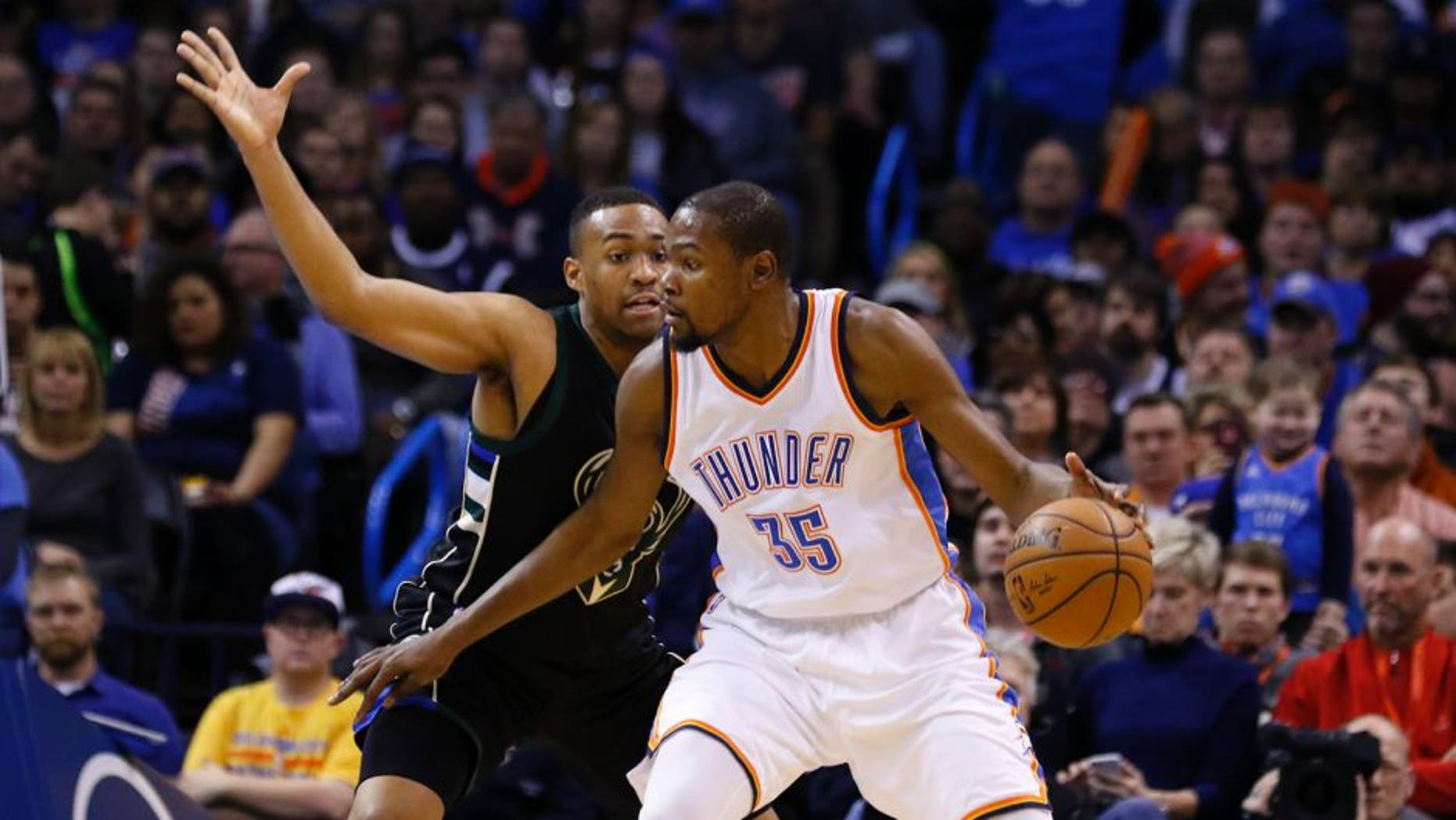 Milwaukee Bucks guard Khris Middleton, left, defends as Oklahoma City Thunder forward Kevin Durant (35) drives to the basket during the first quarter of an NBA basketball game in Oklahoma City, Tuesday, Dec. 29, 2015. (AP Photo/Alonzo Adams)