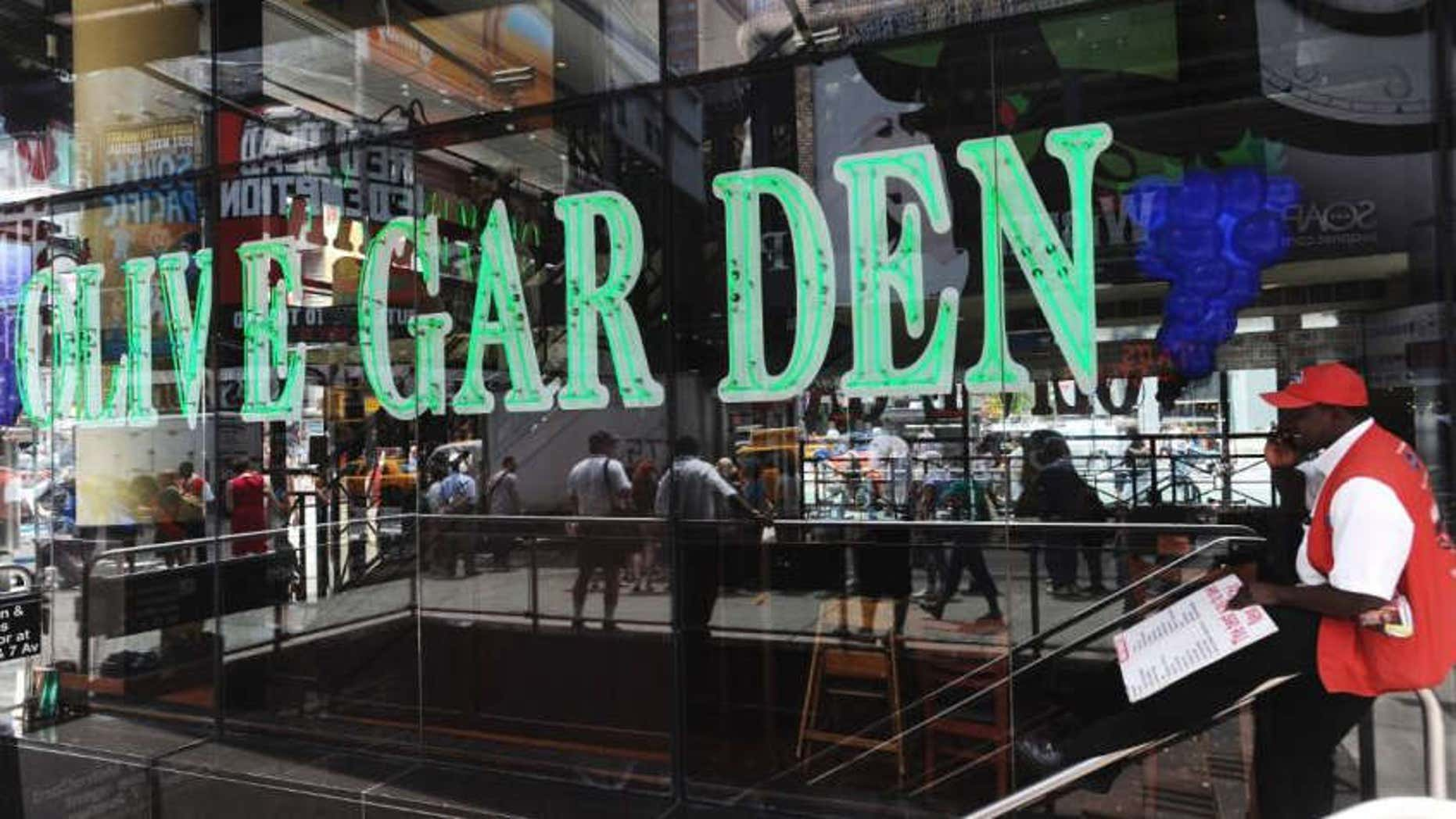A man talks on his mobile phone in front of the Times Square Olive Garden in New York.