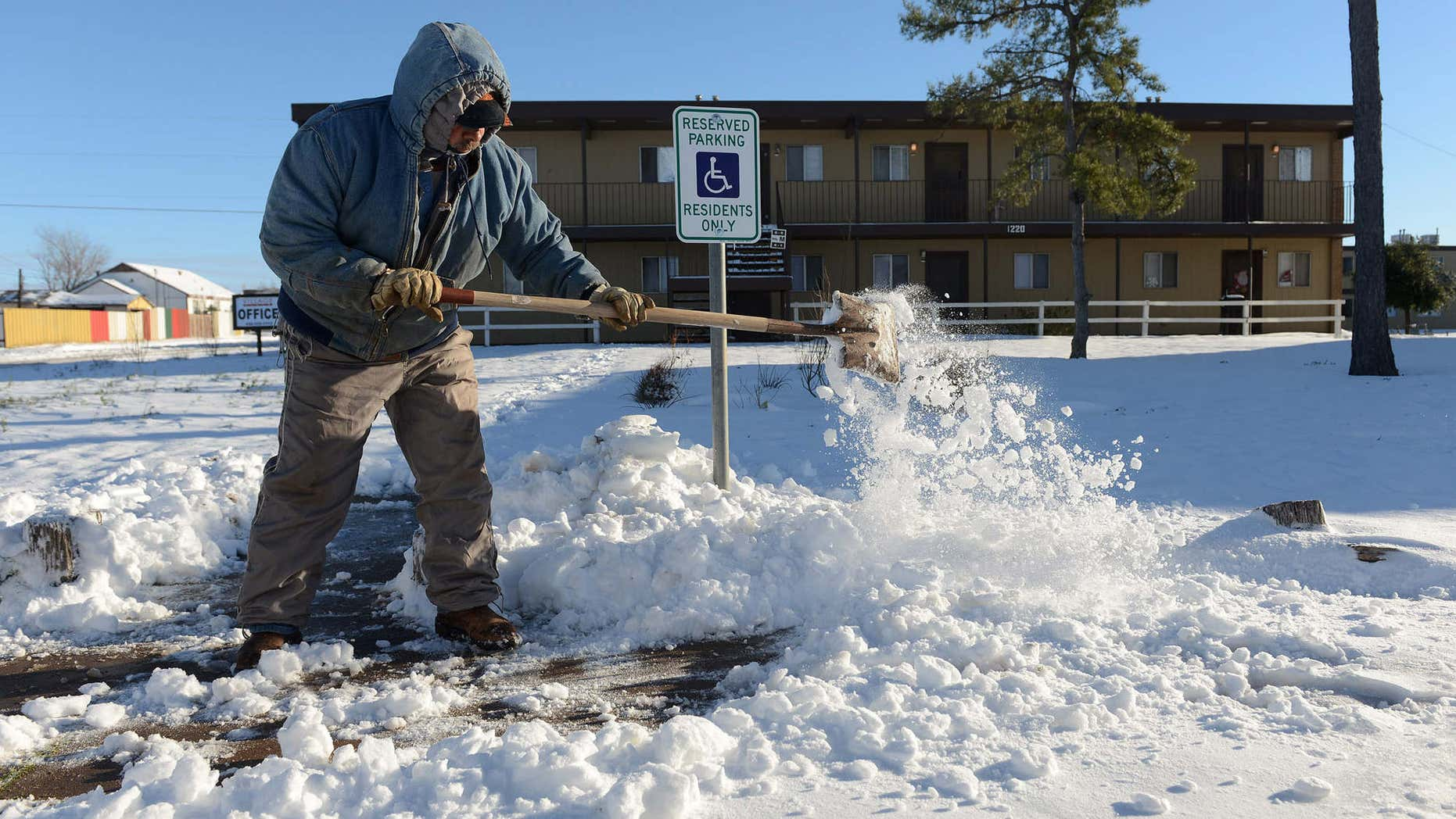 Dec. 28, 2015: Ismael Avelar, maintenance employee for the Village Place Apartments, shovels snow Monday morning from the walkway to the apartment complex office in Odessa, Texas.