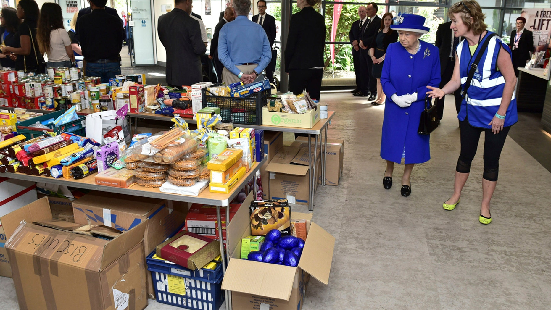 Britain's Queen Elizabeth II, second right, looks at donations made to the members of the community affected by the fire at Grenfell Tower in west London during a visit to the Westway Sports Centre which is providing temporary shelter for those who have been made homeless in the disaster, Friday June 16, 2017.