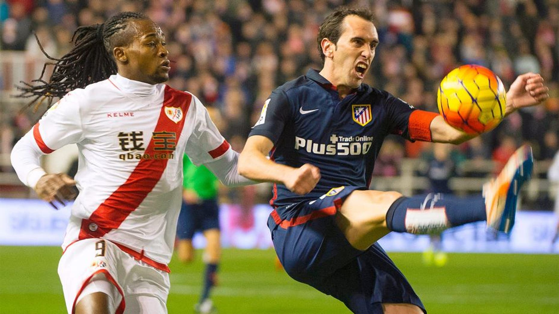 Rayo Vallecano's Angolan forward Alberto Manucho (L) vies with Atletico Madrid's Uruguayan defender Diego Godin during the Spanish league football match Rayo Vallecano de Madrid vs Club Atletico de Madrid at Vallecas stadium in Madrid on December 30, 2015. AFP PHOTO/ CURTO DE LA TORRE / AFP / CURTO DE LA TORRE (Photo credit should read CURTO DE LA TORRE/AFP/Getty Images)