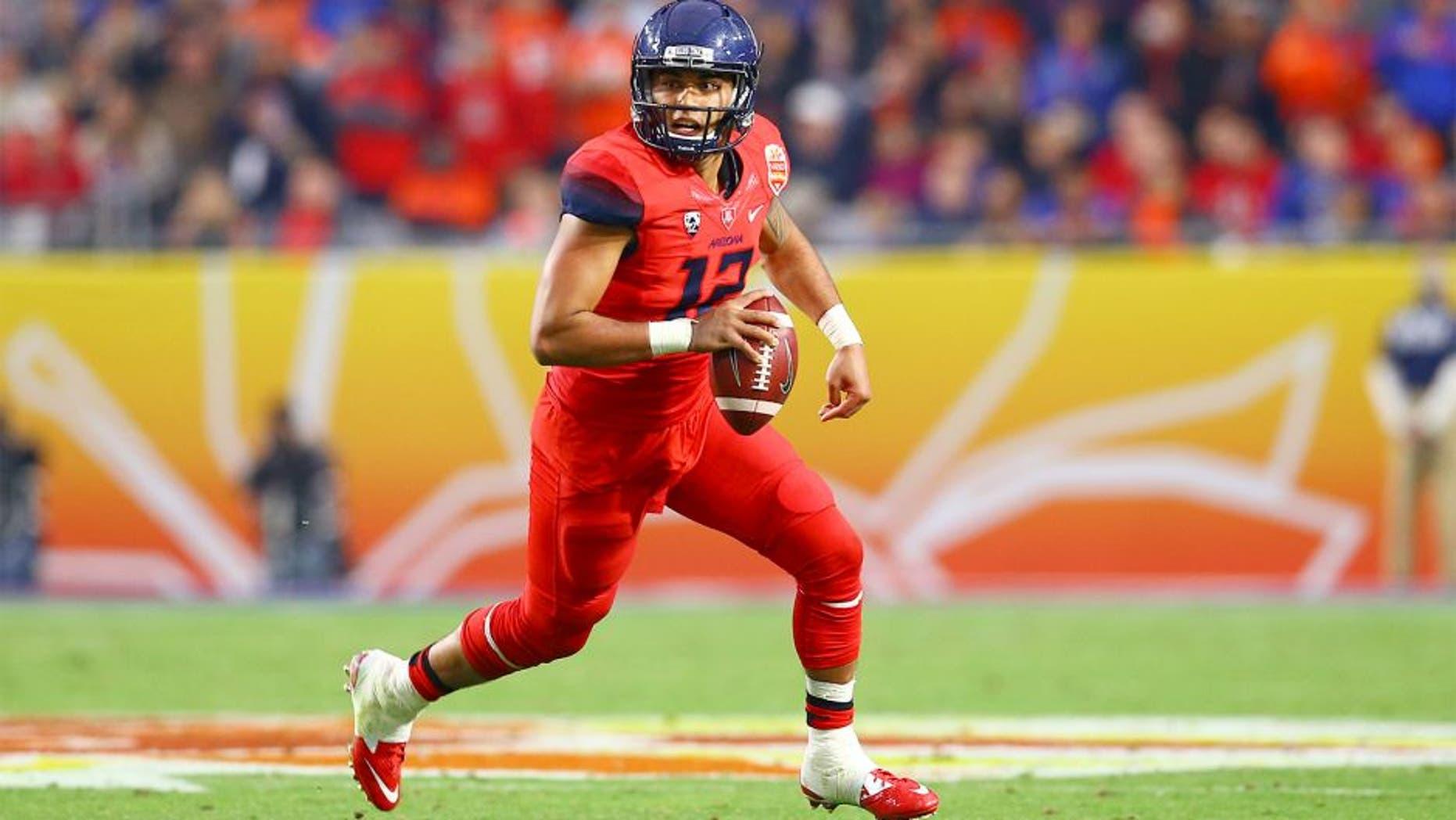 Dec 31, 2014; Glendale, AZ, USA; Arizona Wildcats quarterback Anu Solomon (12) scrambles in the second quarter against the Boise State Broncos in the 2014 Fiesta Bowl at Phoenix Stadium. Mandatory Credit: Mark J. Rebilas-USA TODAY Sports