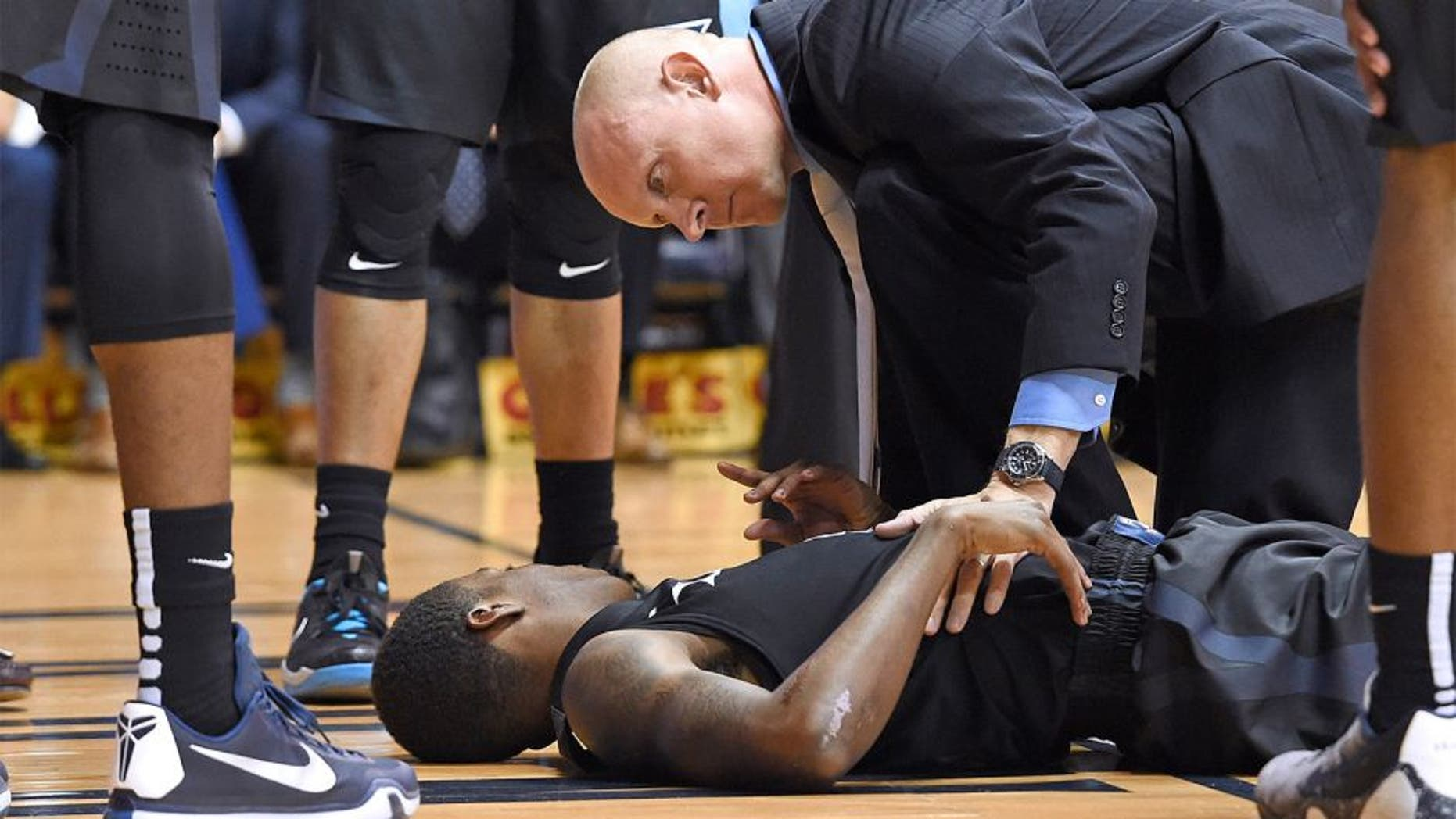 Dec 31, 2015; Villanova, PA, USA; Xavier Musketeers guard Edmond Sumner (4) is checked on by head coach Chris Mack (R) after being injured against the Villanova Wildcats during the first half at The Pavilion. Mandatory Credit: Eric Hartline-USA TODAY Sports