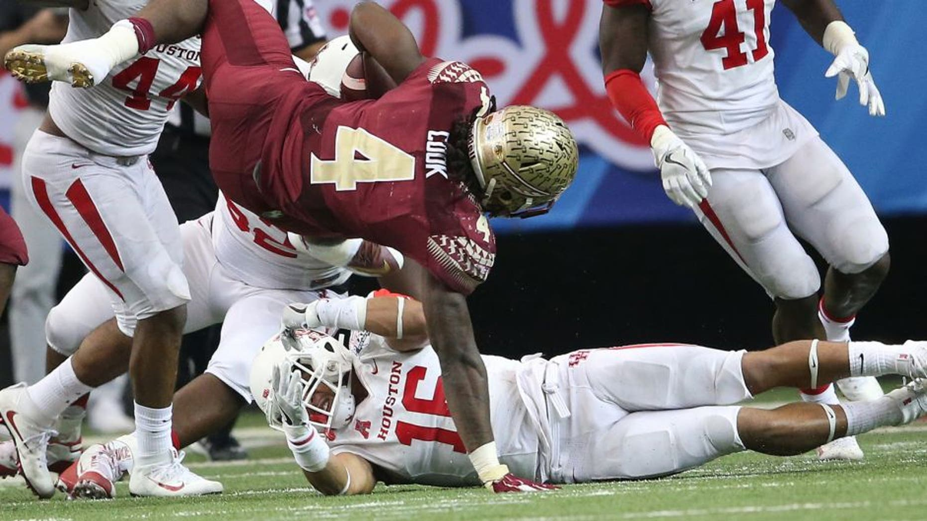 Florida State running back Dalvin Cook (4) falls as Houston safety Adrian McDonald (16) looks on during the second half of the Peach Bowl NCAA college football game, Thursday, Dec. 31, 2015, in Atlanta. (AP Photo/John Bazemore)