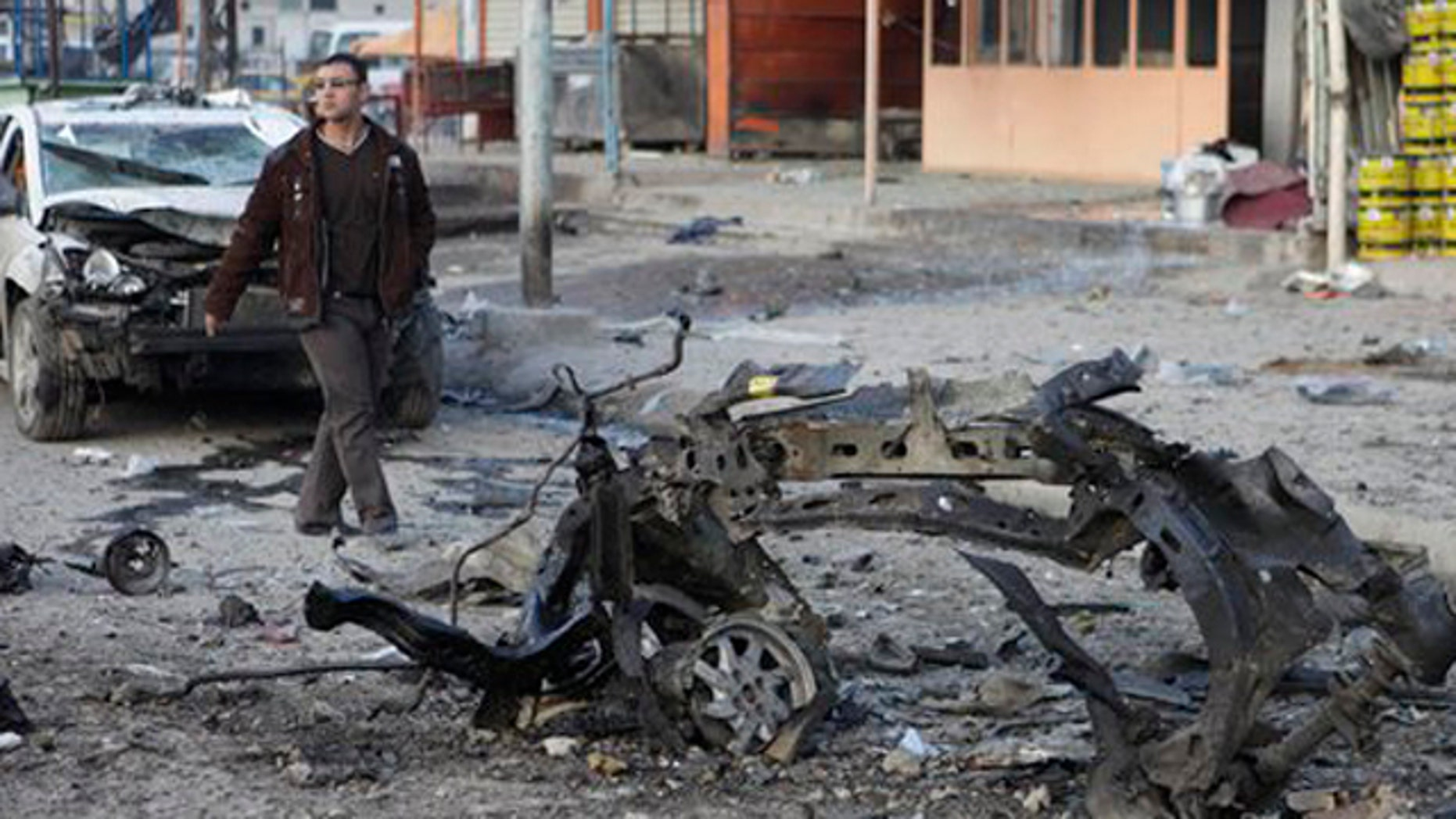 Jan. 24, 2012: A man inspects the scene of a car bomb attack in Sadr City eastern of Baghdad, Iraq.