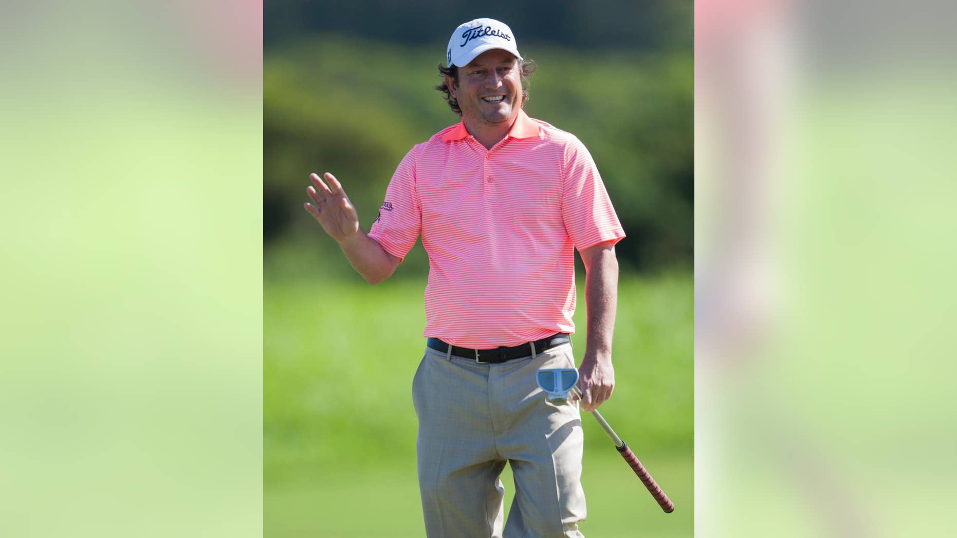 Tim Clark, of South Africa, waves to the gallery after making a birdie putt on the second green during the first round of the Tournament of Champions golf tournament, Friday, Jan. 9, 2015, in Kapalua, Hawaii. (AP Photo/Marco Garcia)