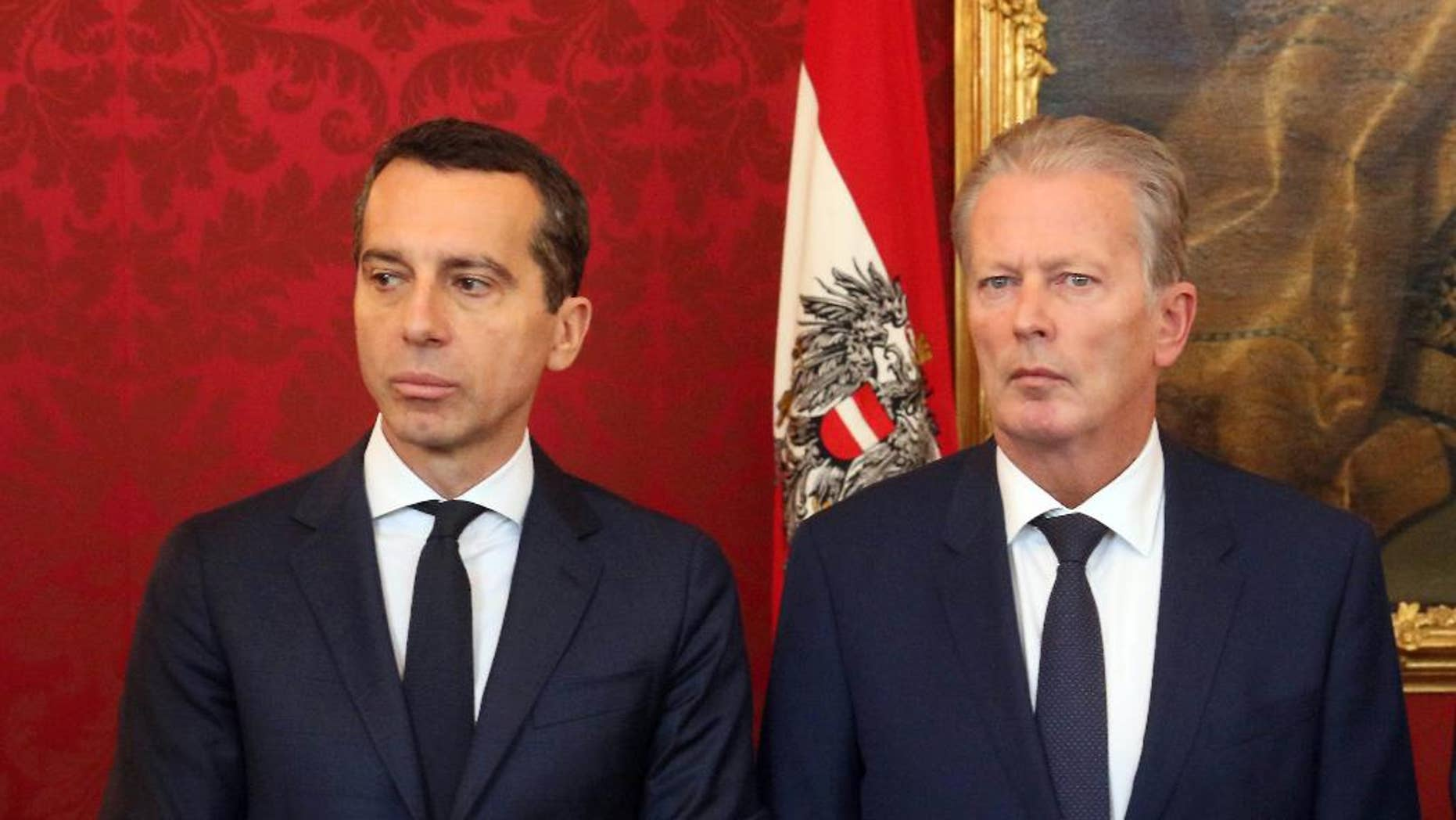 New Austrian Chancellor Christian Kern and Vice Chancellor Reinhold Mitterlehner, from left, attend an inauguration ceremony of four new ministers at the Hofburg palace in Vienna, Austria, Wednesday, May 18, 2016. (AP Photo/Ronald Zak)