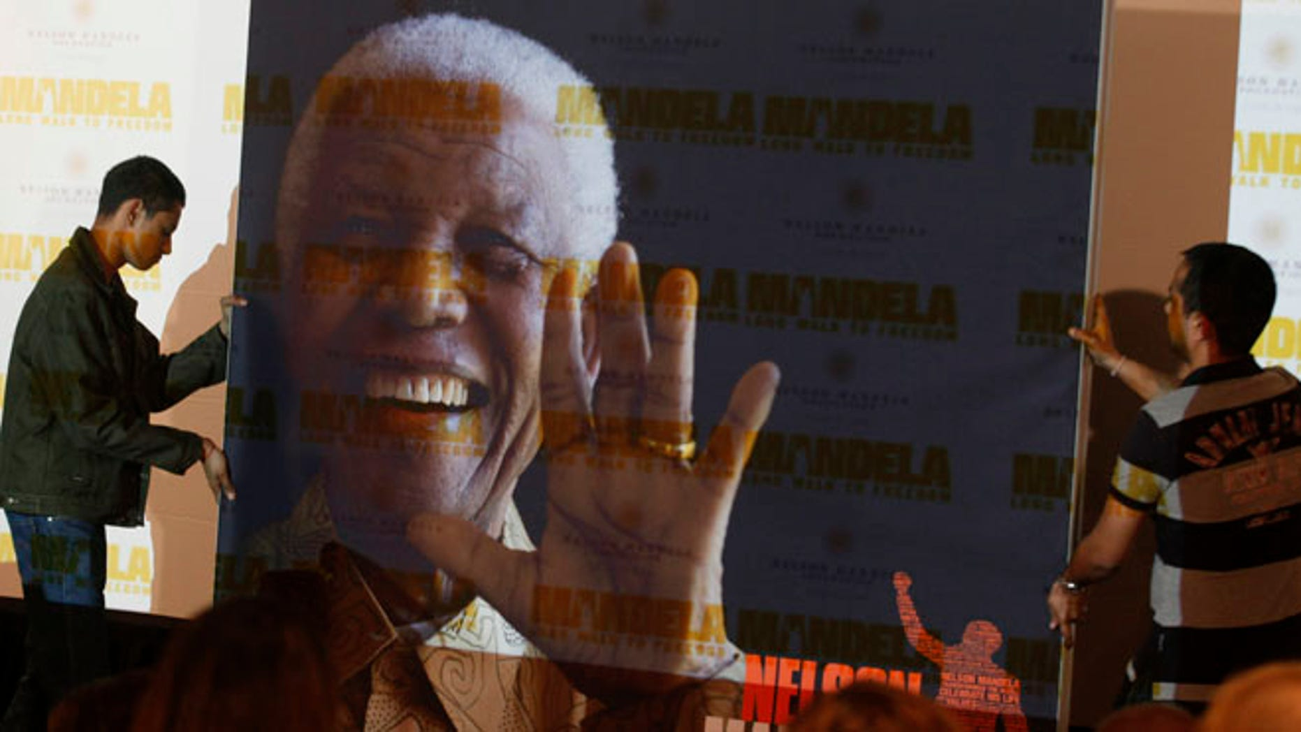 """Nov. 2, 2013: In this file photo, a giant poster of Nelson Mandela is moved to center stage at a news conference held to promote the newly released film """"Mandela: Long Walk To Freedom,"""" in Johannesburg."""